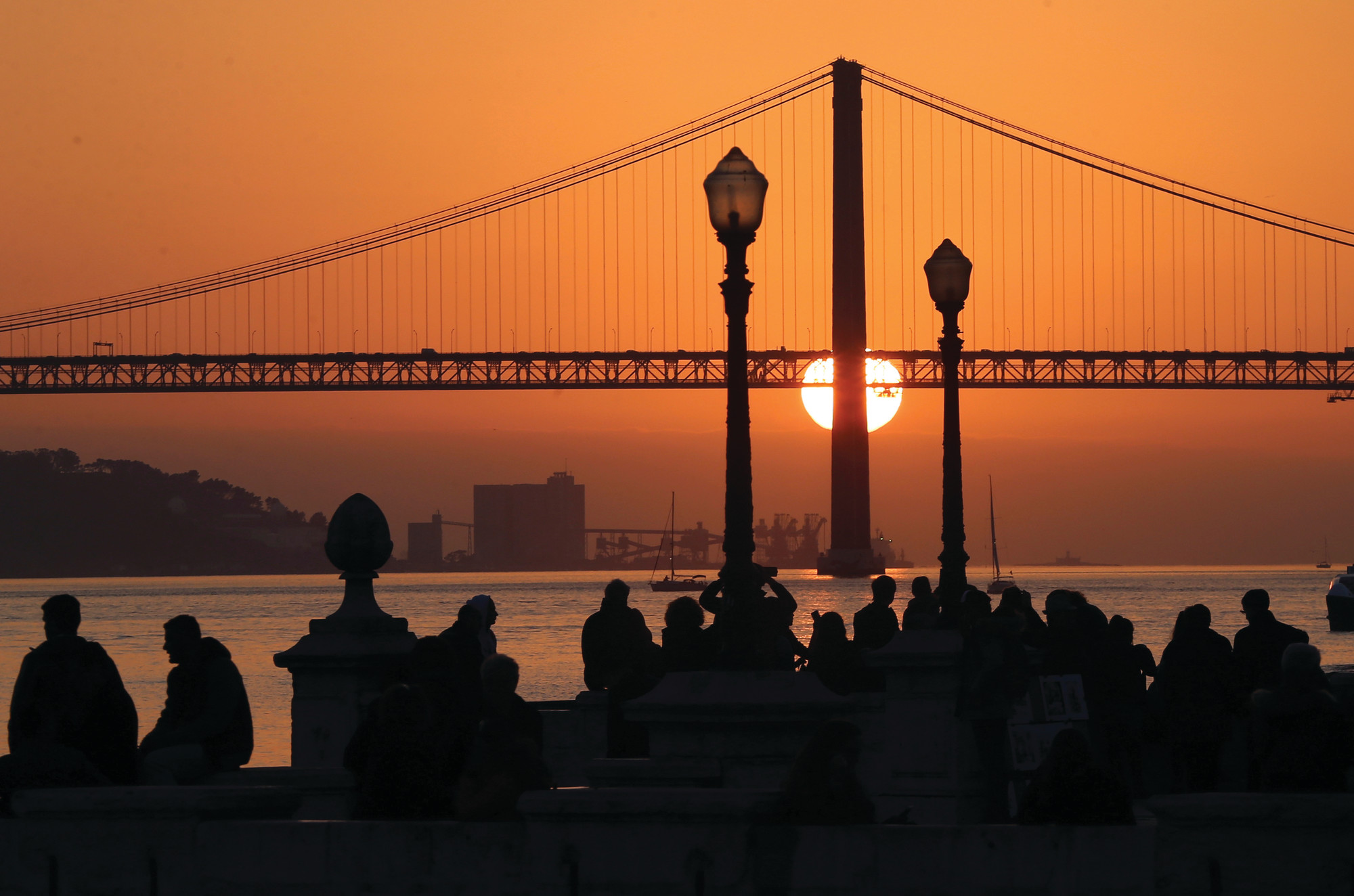THE ASSOCIATED PRESSPeople gather at Lisbon's Comercio square to watch the sun set behind the bridge. A new tour company called Off the Grid, that asks participants put their cellphones away, is launching a trip to Lisbon in July.