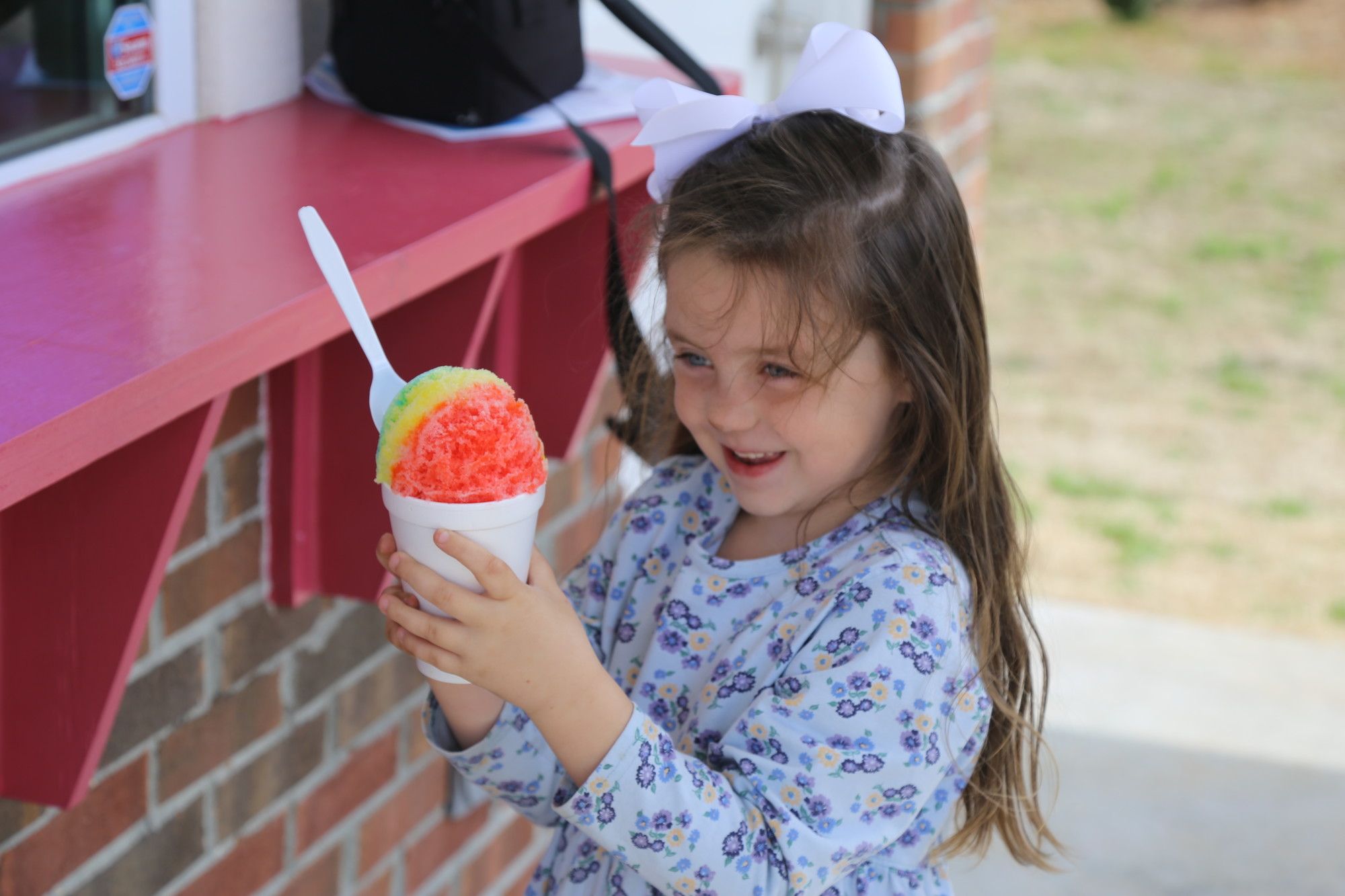 PHOTOS BY BRUCE MILLS / THE SUMTER ITEM Zoey Nelley, 6, enjoys her snowball treat on Monday at Pelican's SnoBalls.