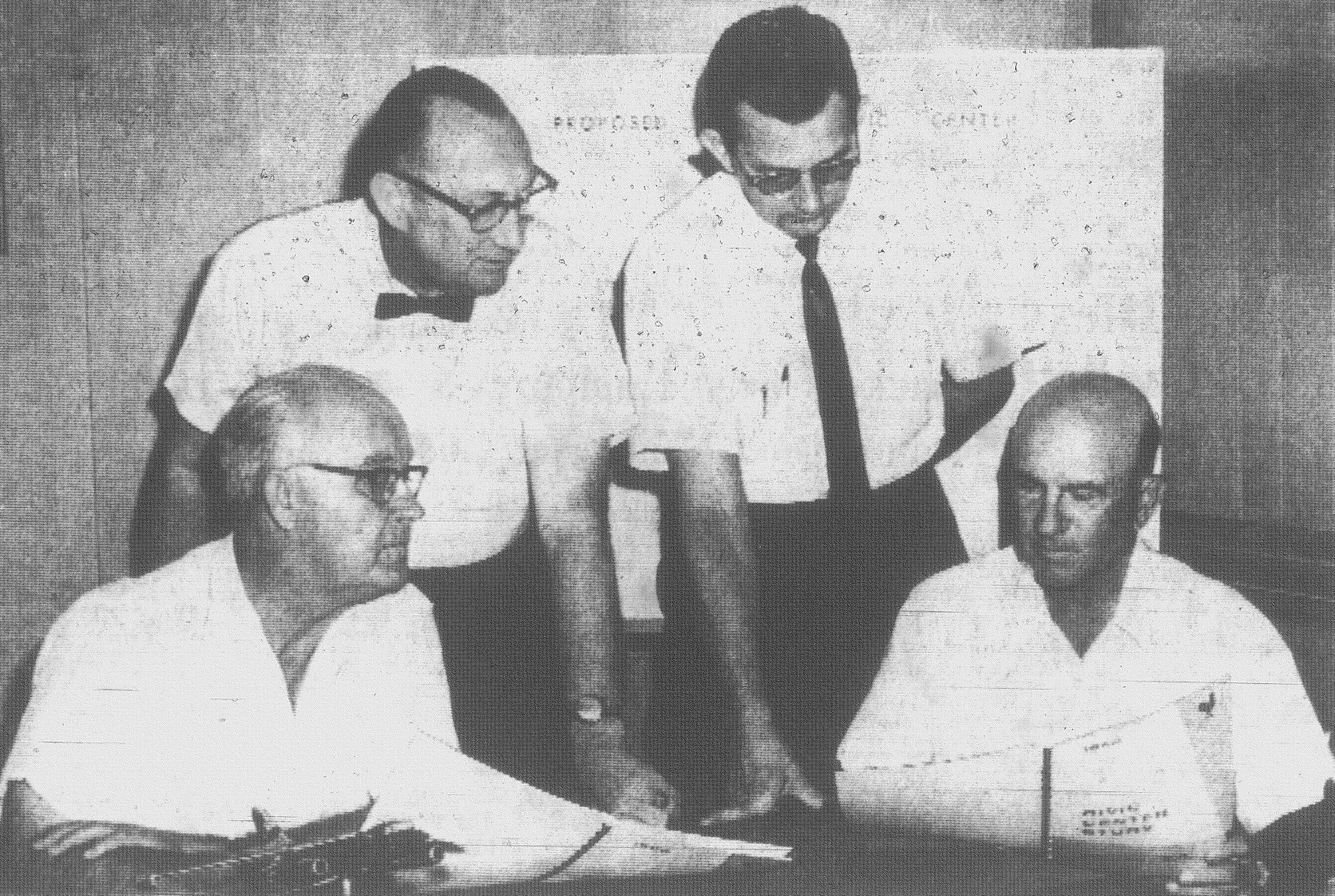Civic Center study committee co-chairmen B.L. Williams and H.D. Osteen (left and right, seated) review their report before the joint meeting of the city and county planning bodies in 1964 at City Hall. The planning bodies adopted the study.