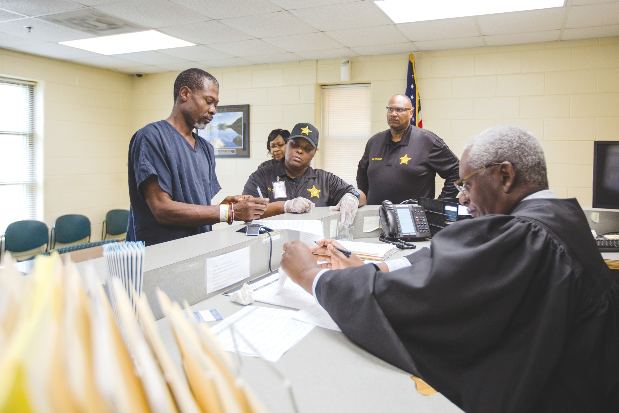 Alonzo Shaw, 50, signs documents during a first appearance hearing lead by Magistrate Judge Larry Blanding at Sumter-Lee Regional Detention Center on Friday.