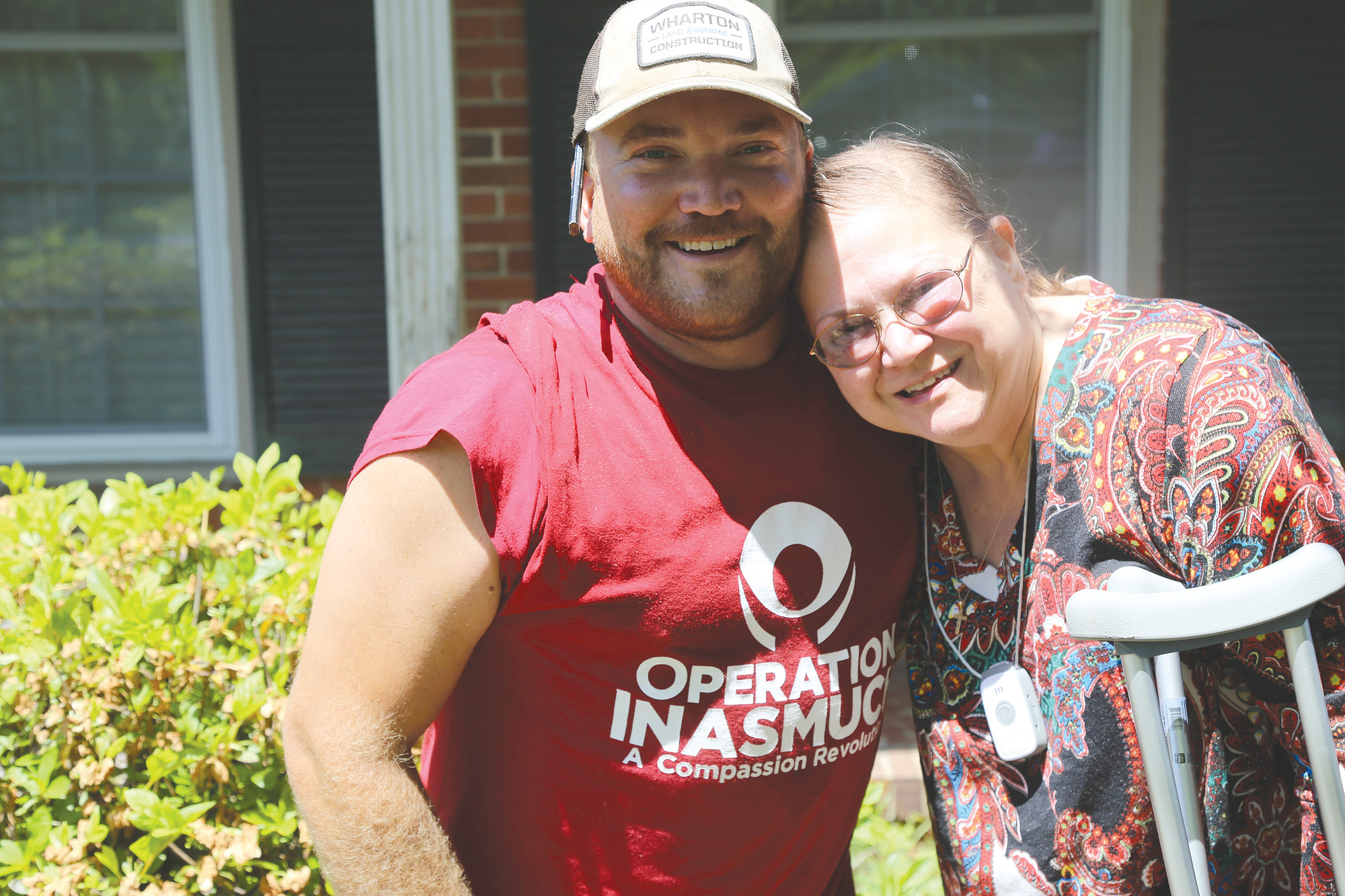 Brandon Wharton, volunteer with Operation Inasmuch on Saturday, hugs Cynthia Bell, whose home he and others made a wheelchair ramp for in order to help Bell get out and about and visit her mother.