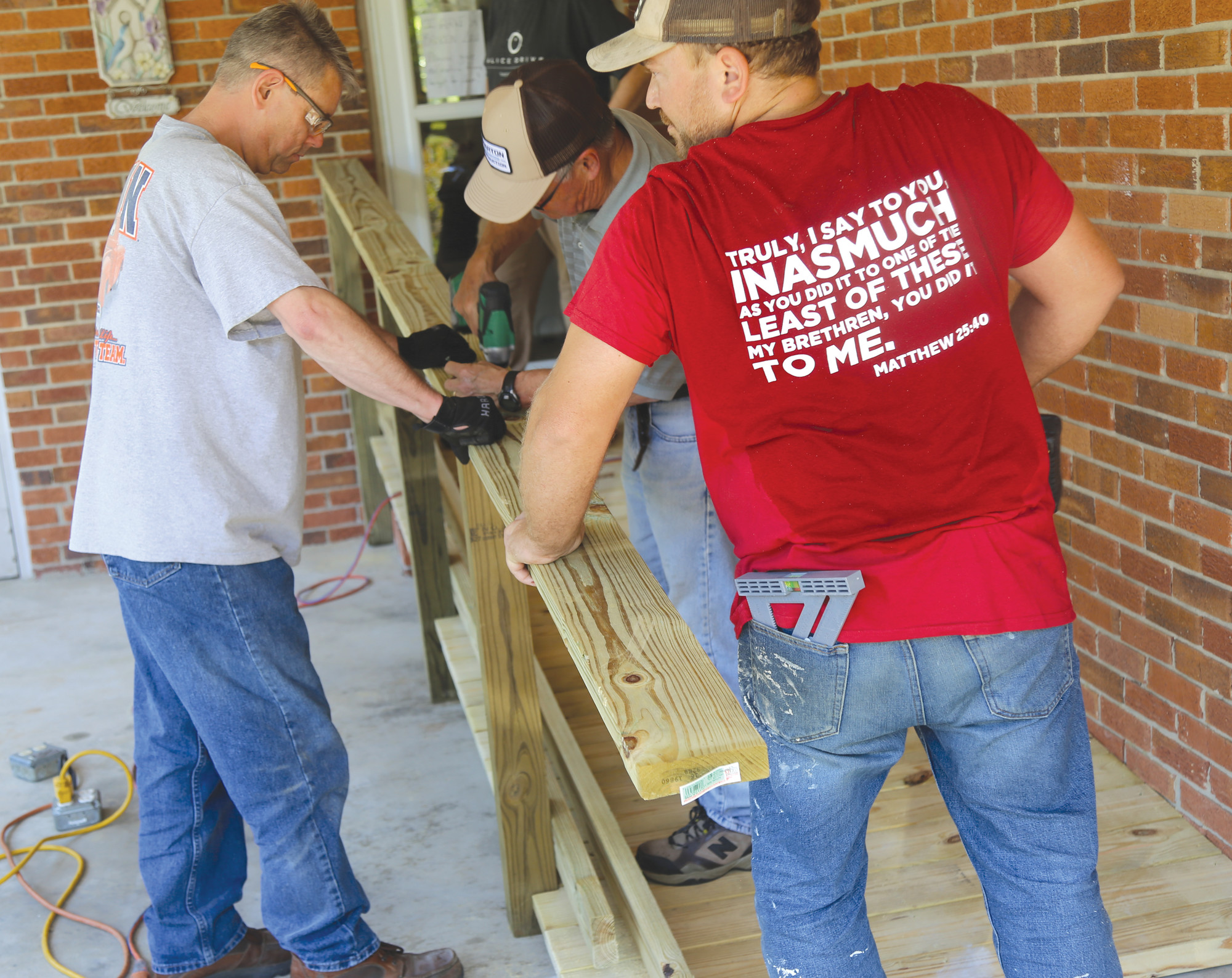 Brandon Wharton leads a team of volunteers Saturday to build a wheelchair ramp at Cynthia Bell's house during Alice Drive Baptist Church's Operation Inasmuch.