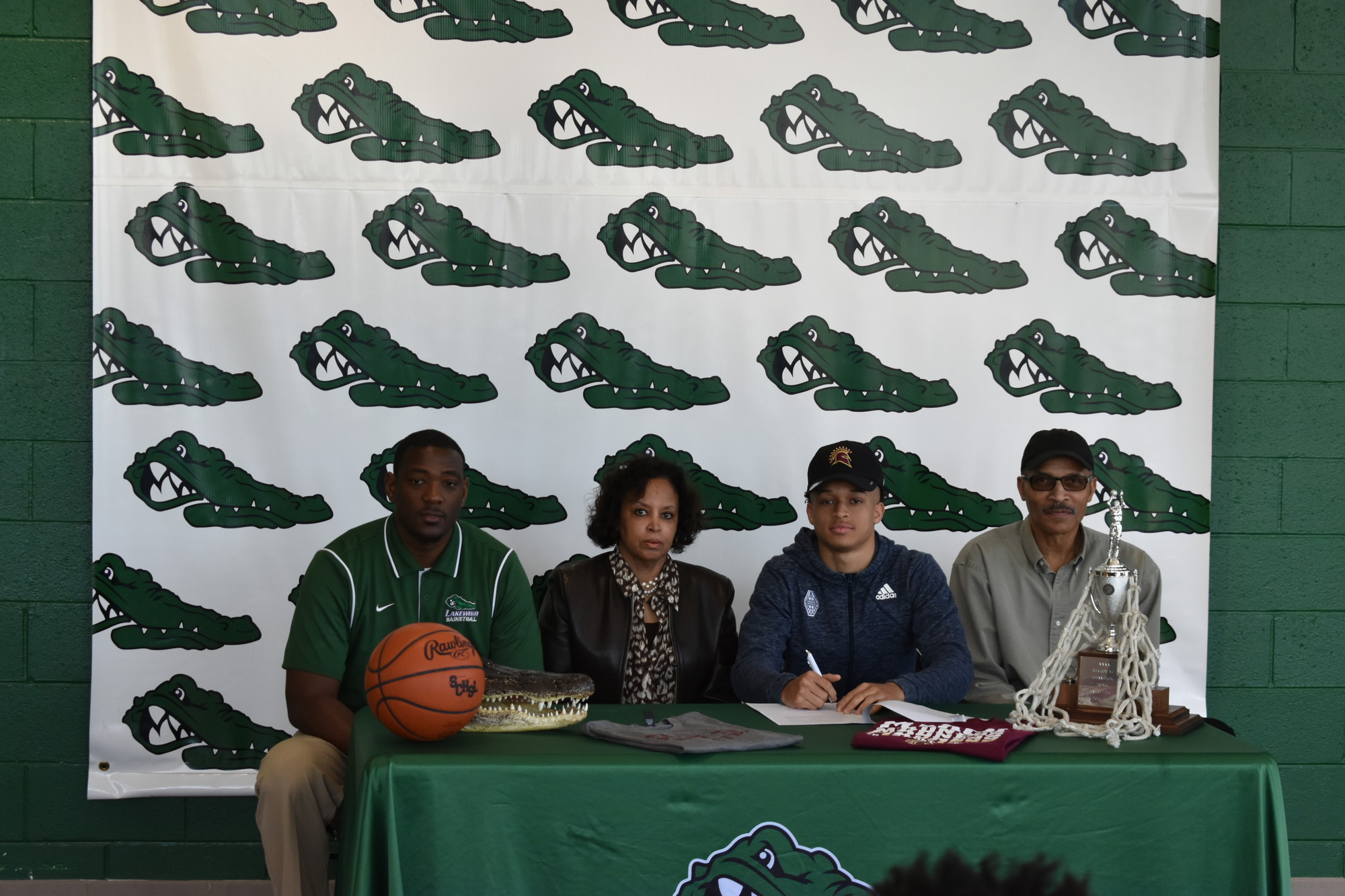Dennis Brunson/The Sumter Item Lakewood High School's Grant Singleton, second from right, has signed to play college basketball with St. Thomas Aquinas College, an NCAA Division II school located in Sparkill, N.Y. Seated with Singleton left to right, are Lakewood head coach Bryan Brown, his mother, Nikki Singleton, and his father, Wilbert Singleton.