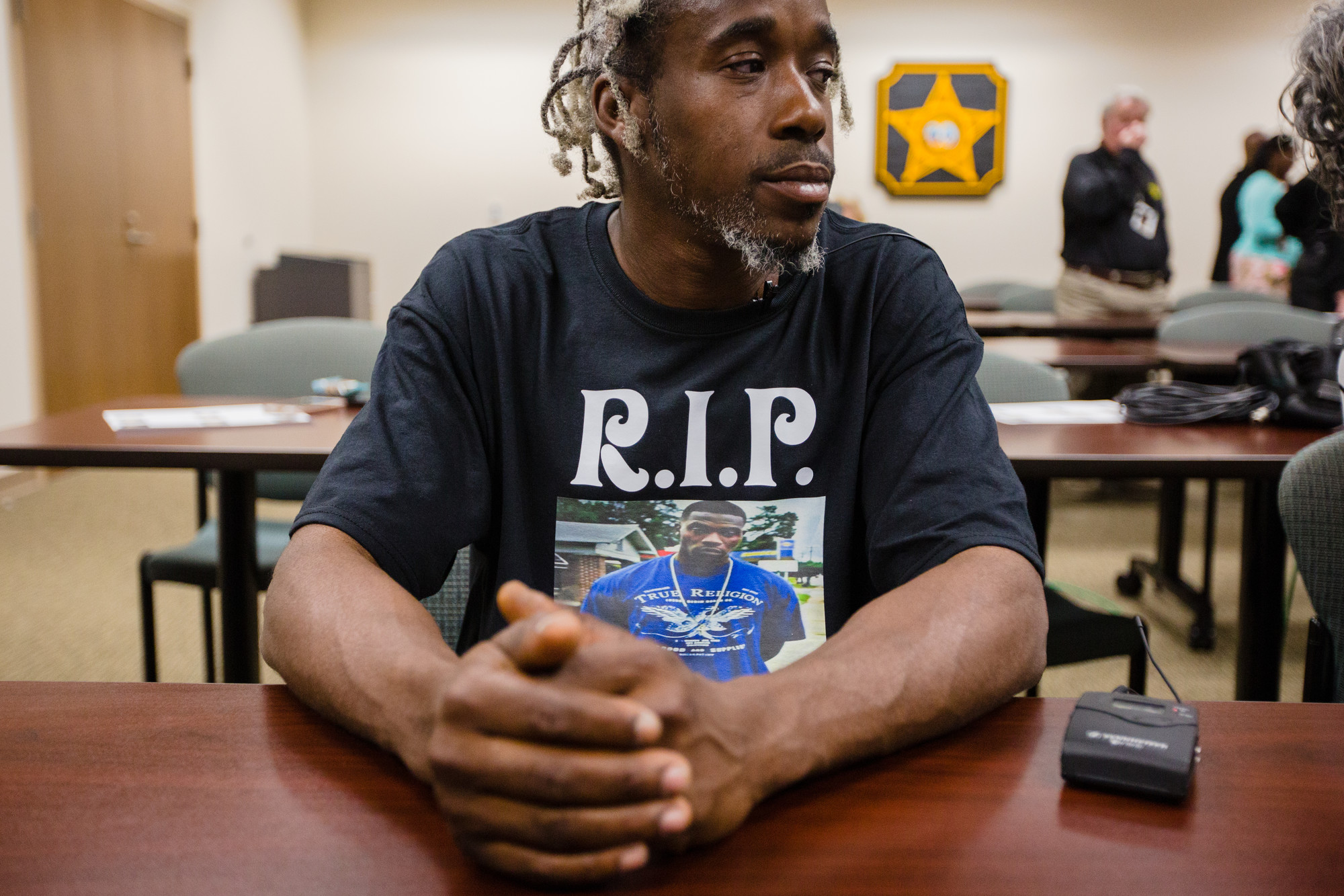 "Darron Brown, the victim's uncle, wears a shirt with Johnson's photo and the words ""RIP Turk"" to the press conference on Monday."