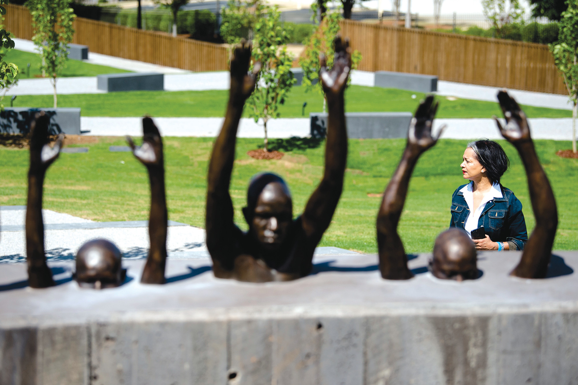 A visitor at EJI's National Memorial for Peace and Justice takes in a sculpture on April 26 in Montgomery. The memorial commemorates 4,400 black people who were slain in lynchings and other racial killings between 1877 and 1950.