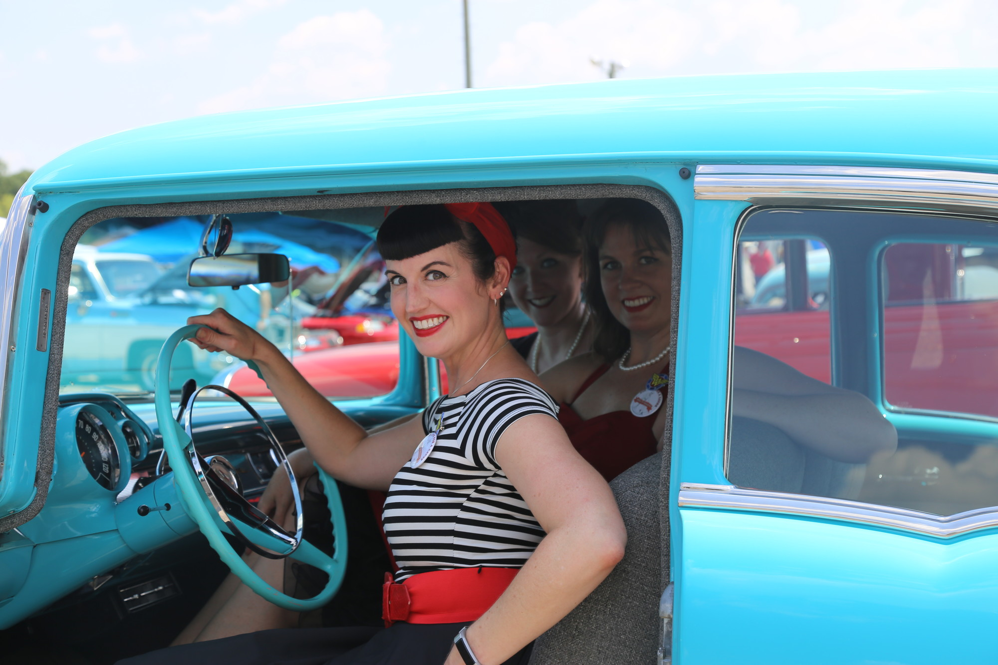 PHOTOS BY KAYLA ROBINS / THE SUMTER ITEMJennifer McKeel, AKA Evie La Fleur, Amy Spear, AKA Kitty Von Kittyn, and Jessica Patton, AKA General Patton, all of Pin Ups For a Cause South Carolina Chapter, try out one of the cars on display on Saturday at the Hot Pursuit BBQ Cook-off and Car Show. The group advocates for anti-bullying in Charleston.