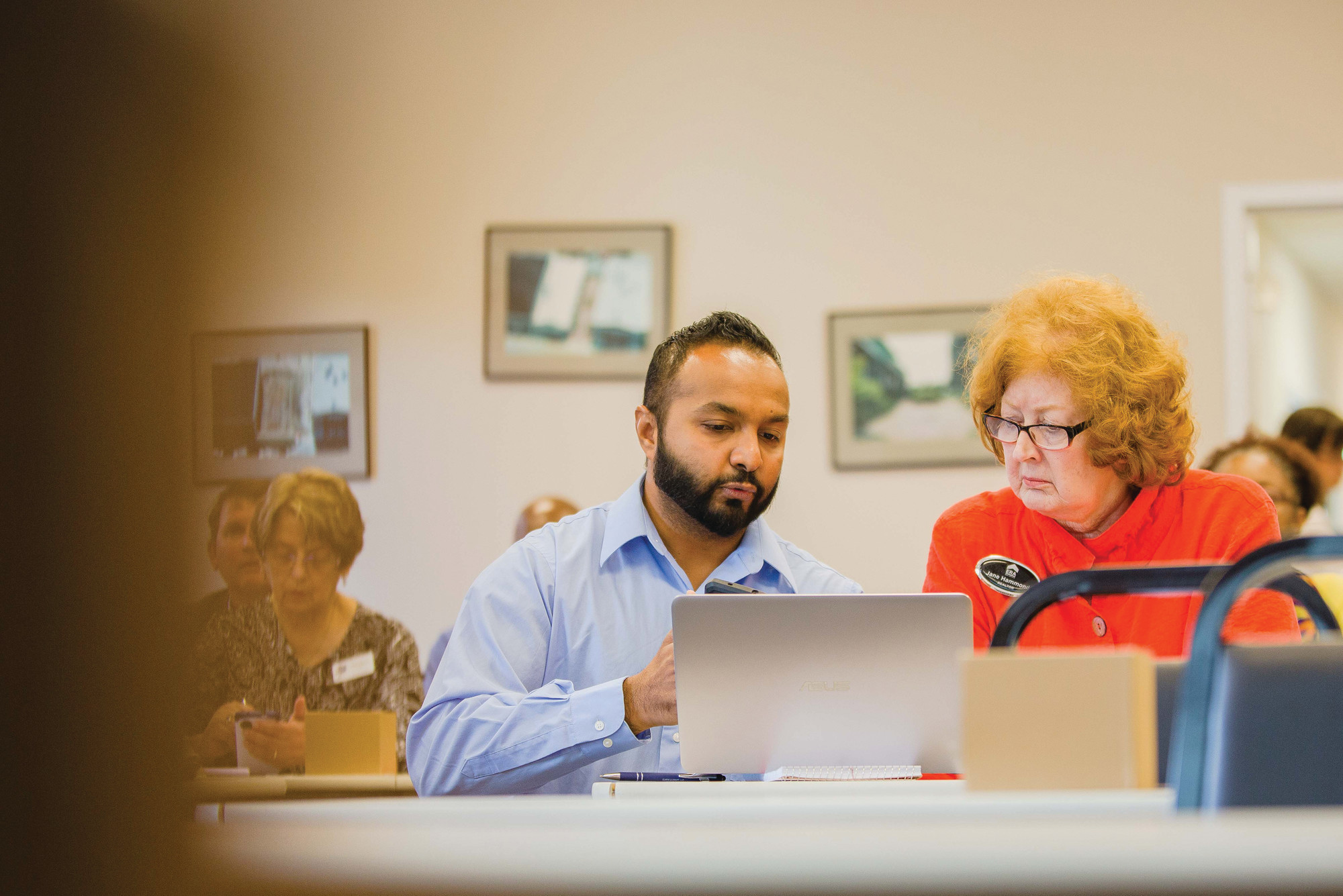 Anand Vora, left, founder of the PORCHD mobile device application, assists local Realtor Jane Hammond with using the app on Wednesday during a briefing on the newly released product.