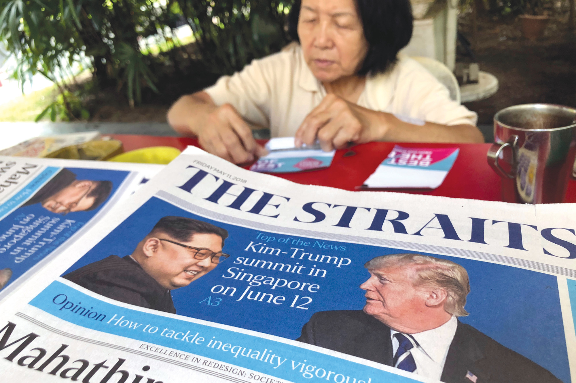 A news vendor counts her money May 11 near a stack of newspapers with a photo of U.S. President Donald Trump, right, and North Korea's leader Kim Jong Un on its front page  in Singapore.