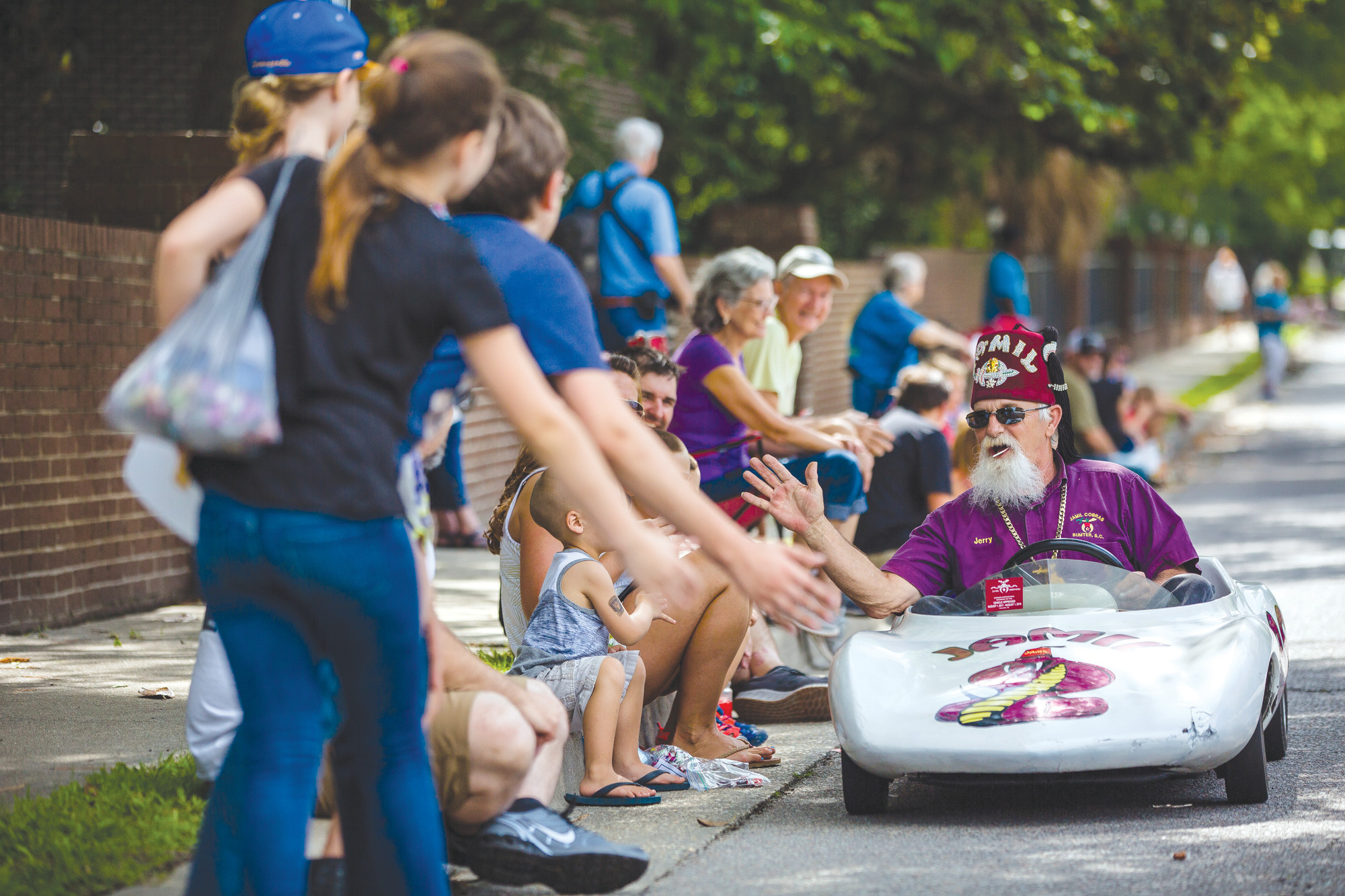 A member of the Shriners gives high fives as he passes in his little car during a past Iris Parade at Swan Lake-Iris Gardens in Sumter.