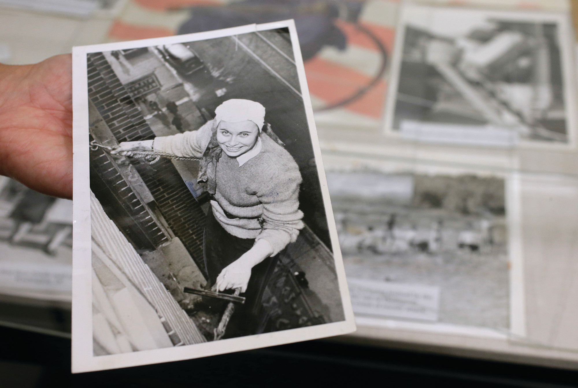 PHOTOS BY THE ASSOCIATED PRESSSue Wilkins, director of education at The International Museum of World War II, holds a 1945 newspaper photograph at the museum in Natick, Massachusetts, that shows Fern Corbett, 24, working as a window washer 10 floors above a Minneapolis street during World War II.