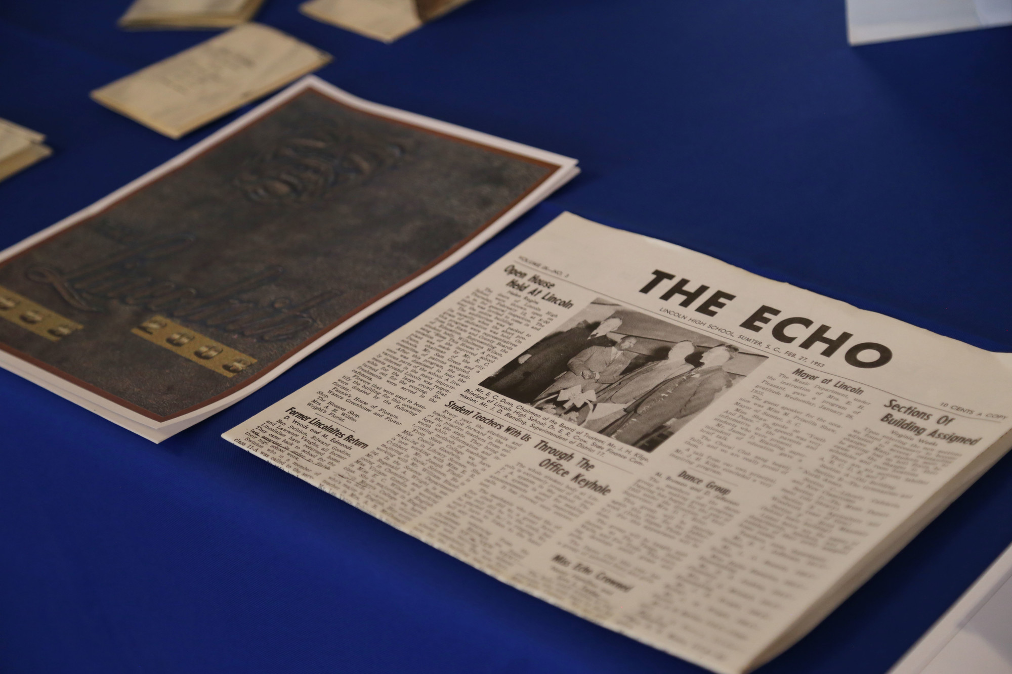 A copy of the high school's paper, The Echo, sits on the table in front of old photos of students at the dinner on Tuesday.