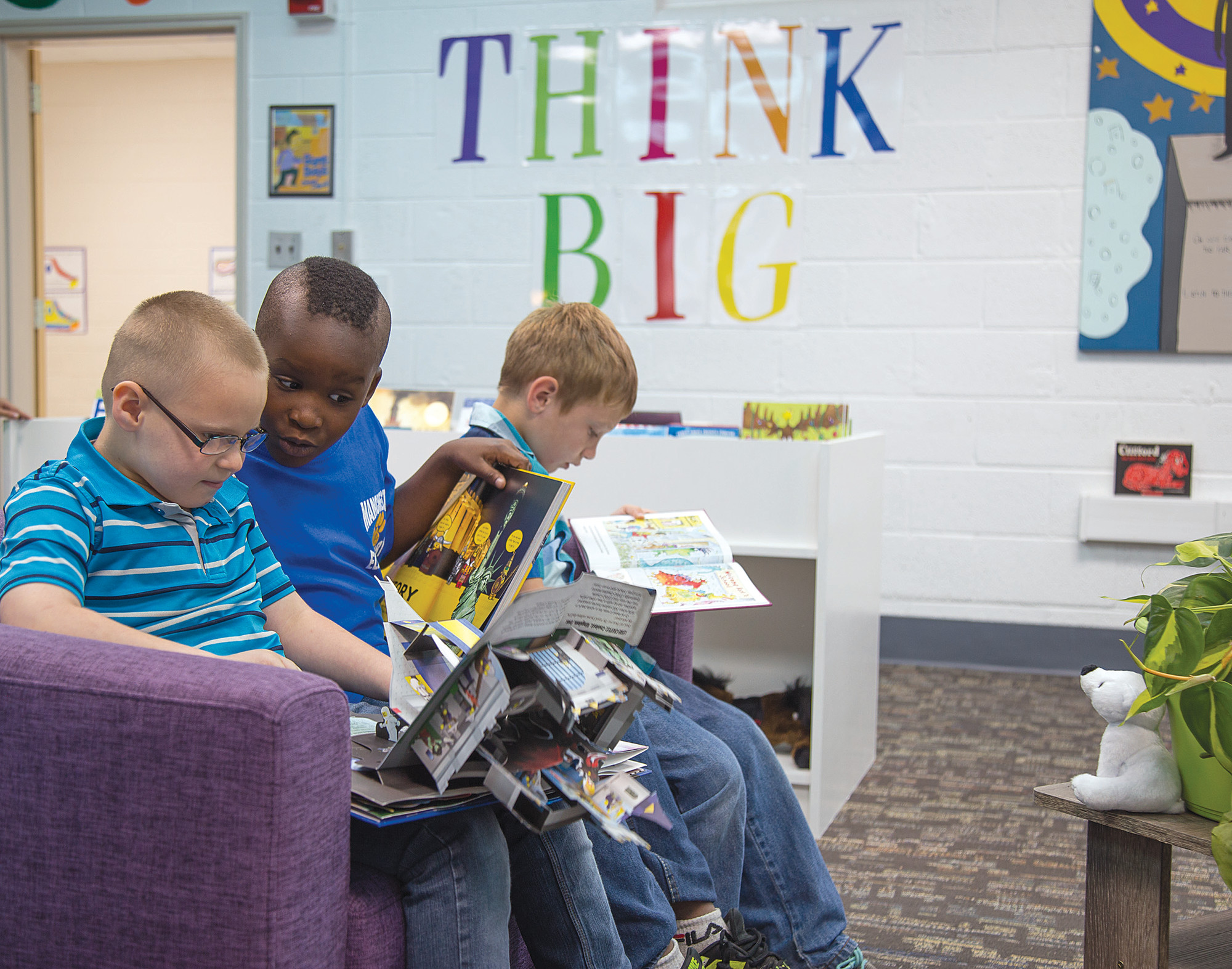 From left, first-graders Donovan Talbott, Christopher Hardy and Kyler Kee read books in the new Ben Carson Reading Room at Manchester Elementary School on Tuesday.