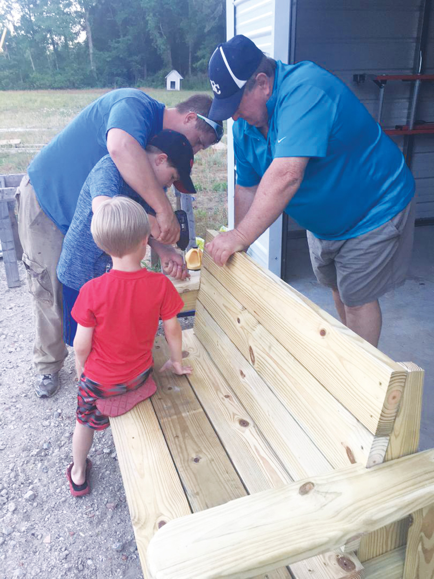 PHOTOS PROVIDEDColin Myers helps his father, Nick Myers, build a Buddy Bench as his brother, Evan, and his grandfather, Benton Blakely, offer their help.