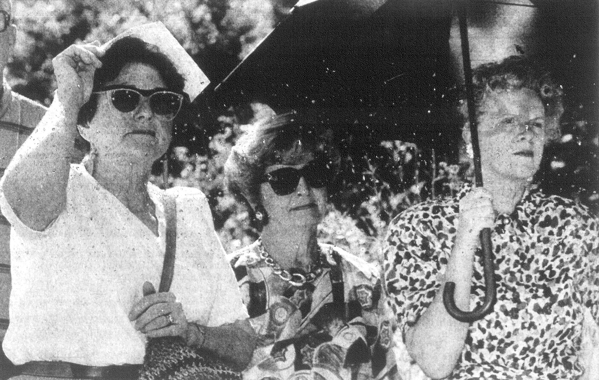1993 - Cile Moise, left, uses a program to shield her head from the sun while Anna Bynum and Betty Brogdon seek shelter under an umbrella while listening to speeches during groundbreaking ceremonies for Covenant Place retirement home.