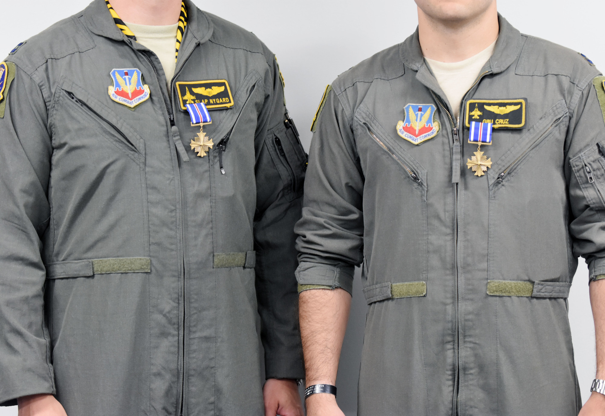 The blue Distinguished Flying Cross Medal hangs from the chests of Capts. John Nygard and Salvador Cruz.