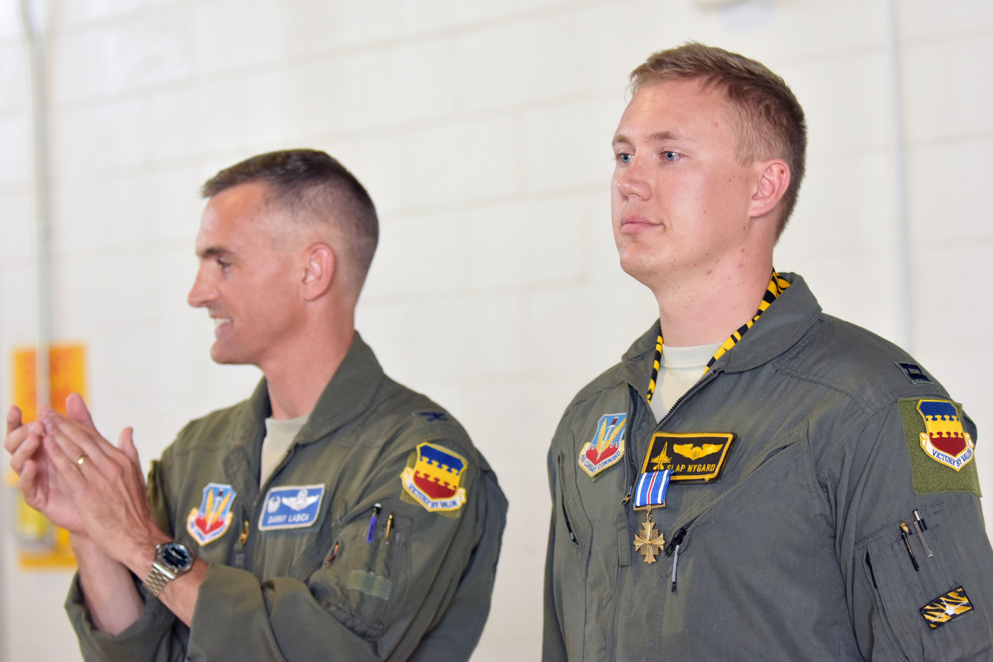 Col. Daniel Lasica applauds Capt. John Nygard after pinning his DFC Medal on Thursday at Shaw Air Force Base.
