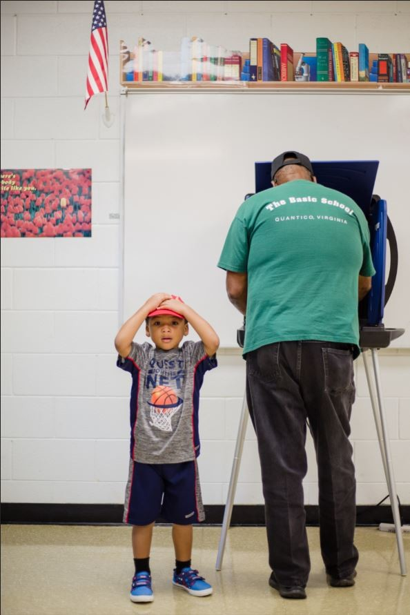 Larry Corbet waits on his grandfather Danny Williams to finish voting at the Wilson Hall voting precinct.