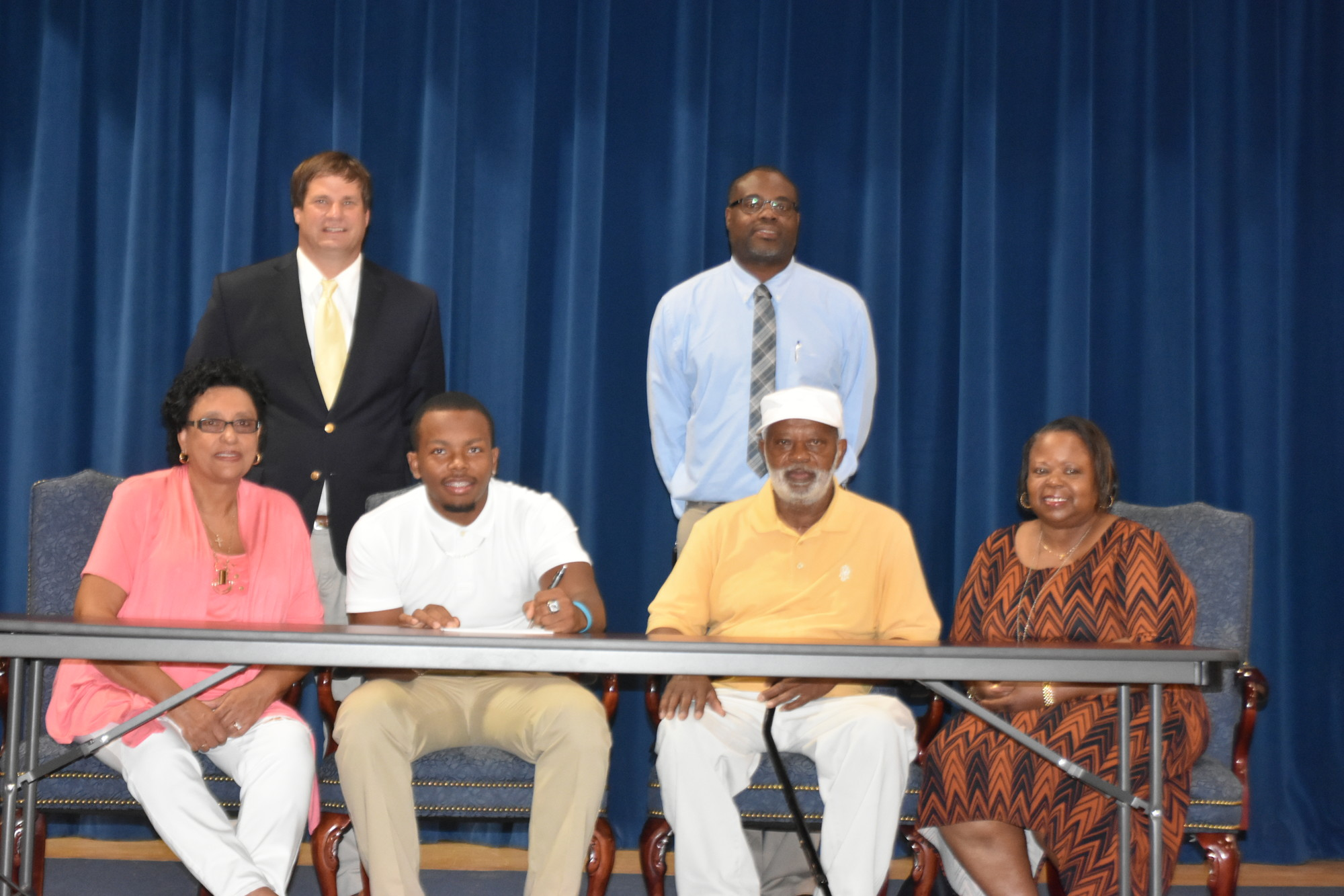 Joshua Pringle of Scott's Branch High School, seated second from the left, has signed with South Carolina State University in Orangeburg to compete in both track and field and football. Seated with Pringle, from left to right, are mother Judy, father Joshua Sr. and aunt Patricia. Standing are Scott's Branch athletic director and football head coach Brian Smith and track and field head coach Kevin Miller.
