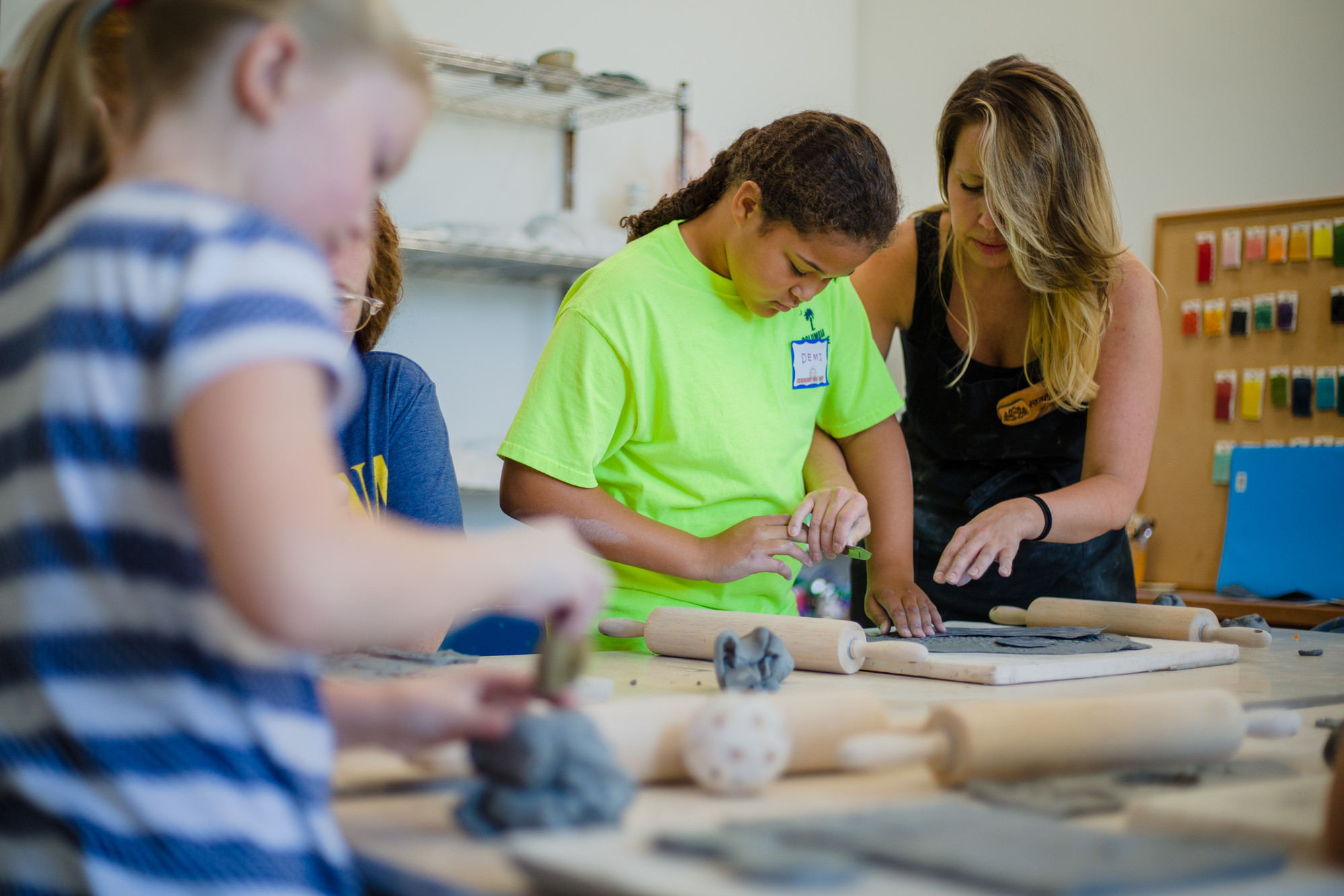 Morgan Edwards helps Demi Crawford with cutting clay during the summer youth pottery class Tuesday at Sumter County Gallery of Art.