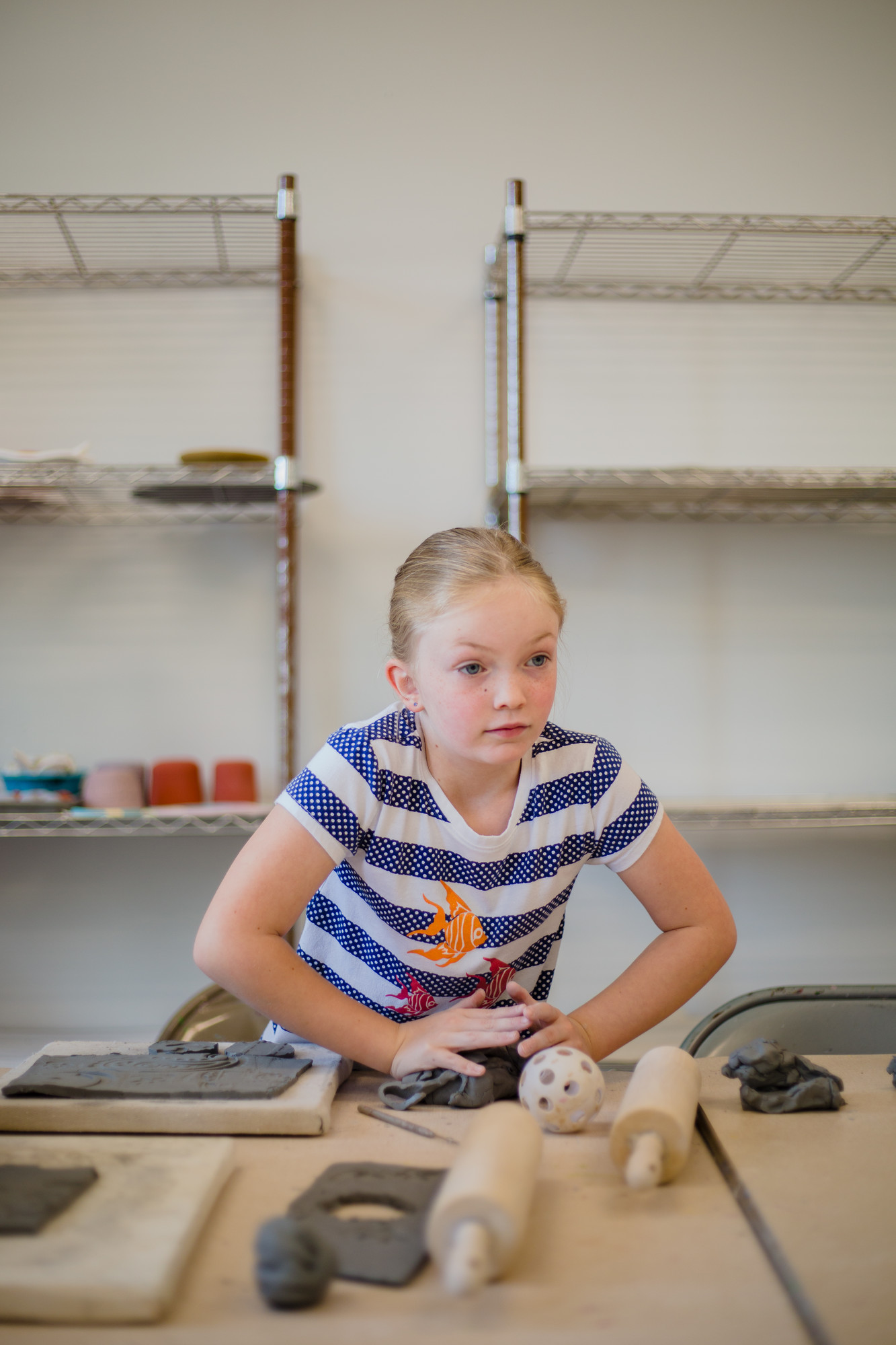 Ellie Flynn works to mold excess clay between projects on Tuesday.