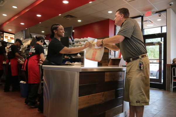 Arby's shift manager Dalexus Dingle, left, hands customer Boyce Hodge his food order Wednesday during the new restaurant's first day of business at 1954 McCrays Mill Road.
