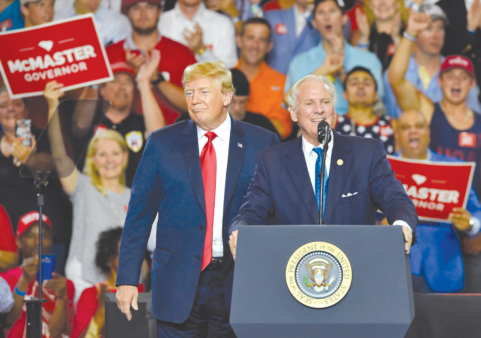 In this Monday, June 25, 2018, file photo, South Carolina Gov. Henry McMaster, right, with President Donald Trump, speaks to the crowd at Airport High School in West Columbia. McMaster, one of Trump's earliest and most loyal supporters, won a key runoff in the June primary as he fended off a challenge from John Warren, a self-made millionaire, to secure the Republican gubernatorial nomination. (AP Photo/Richard Shiro)