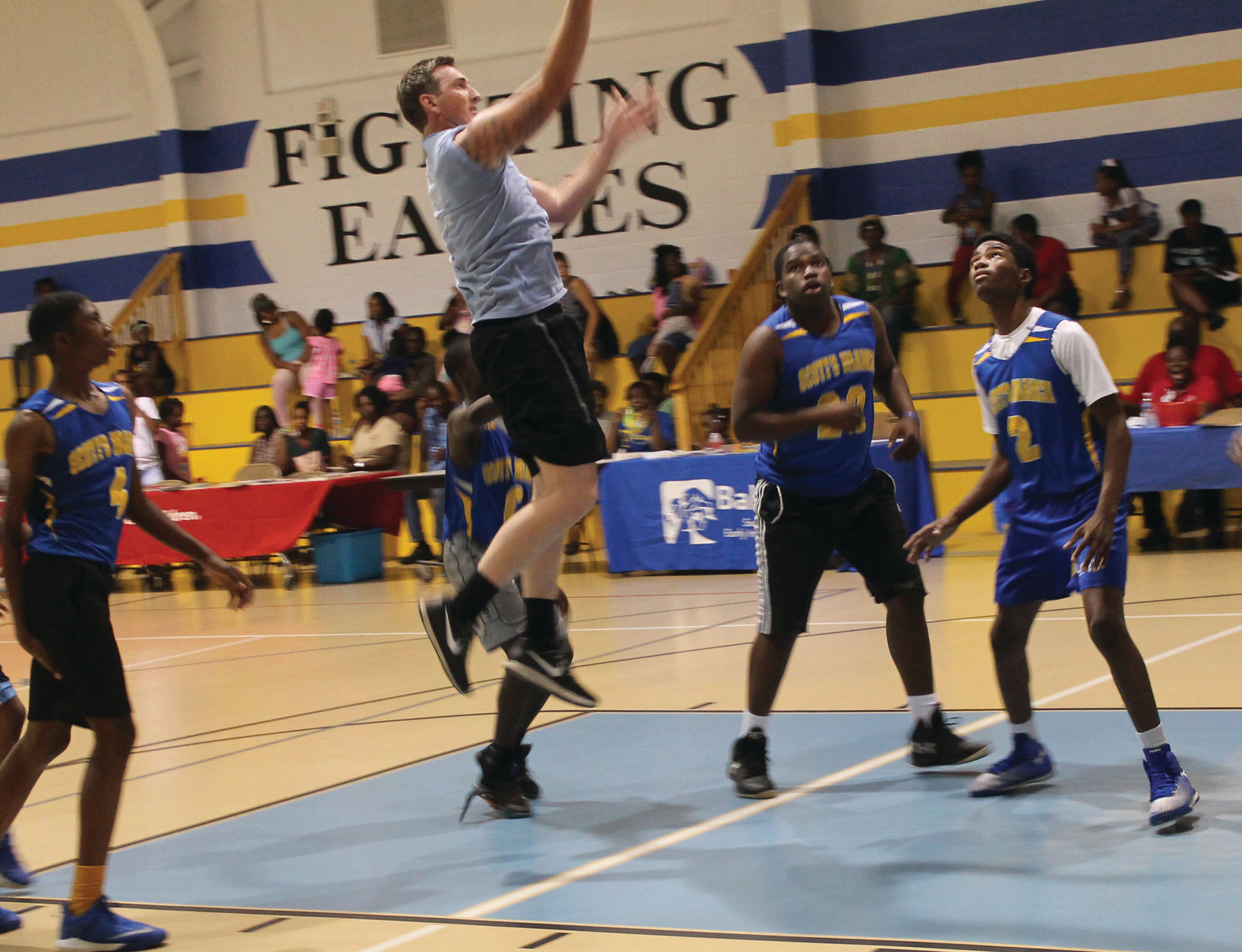 Athletes from Scott's Branch High School look on as CCSO Deputy Shane Ballard takes it to the hoop during the game at the event.