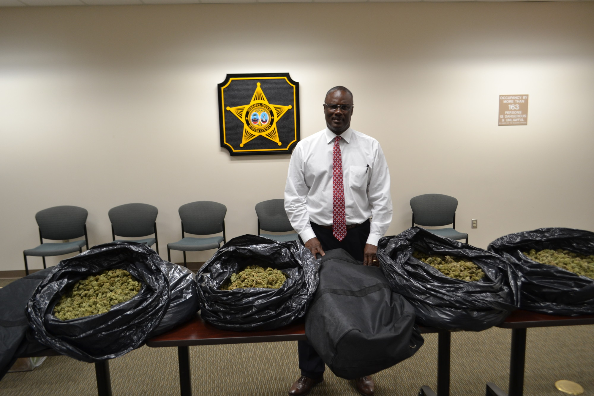 Sumter County Sheriff Anthony Dennis stands with some of the marijuana seized during Operation Ice Storm.