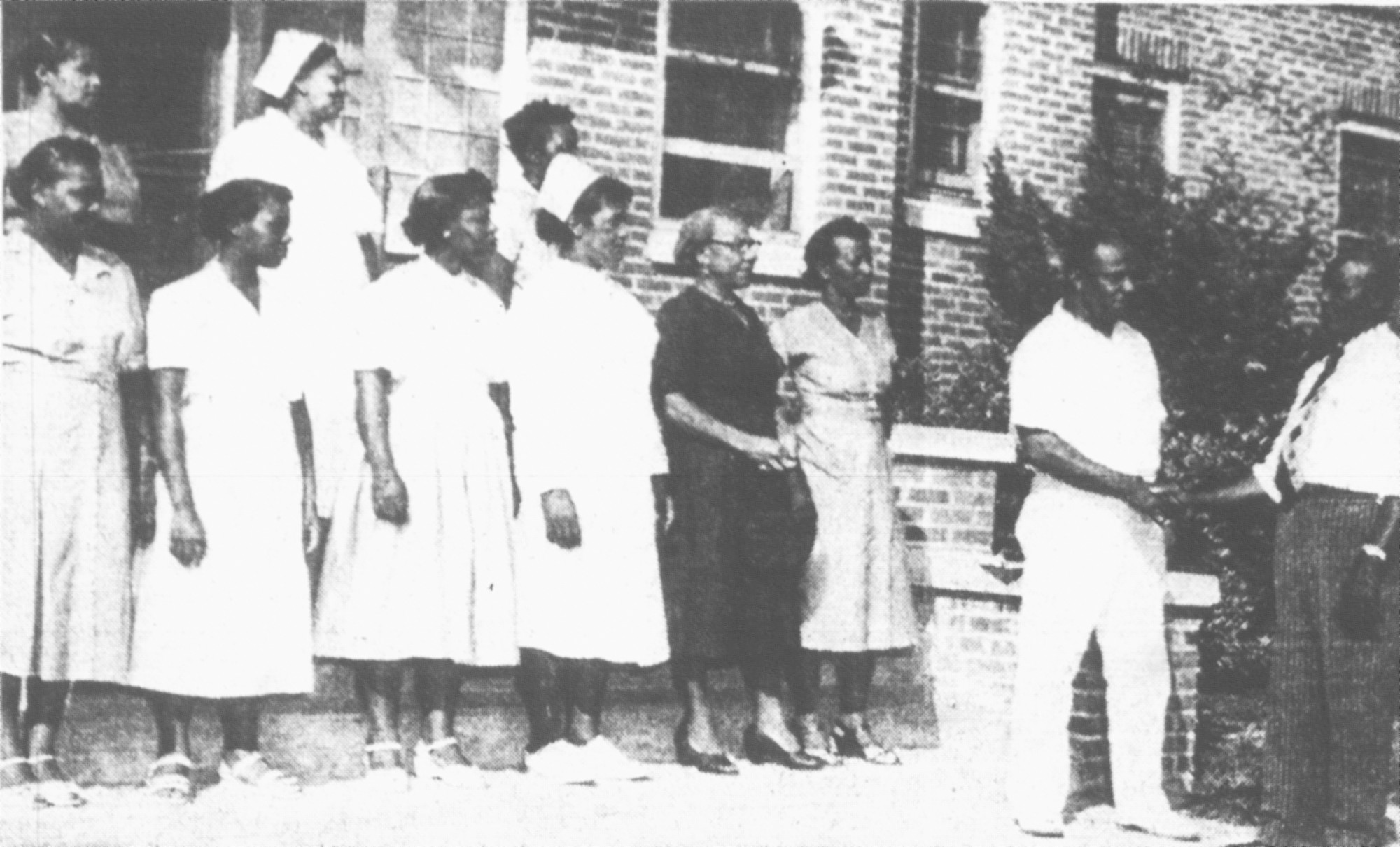 Rev. H.B. Brown, far right, welcomes Dr. William L. Johnson to the staff of Sumter Community Hospital. Dr. Johnson came to Sumter from the Norfolk, Virginia, Community Hospital. Other staff members pictured are: front row, from left, Margurite B. Mickens, Trula Mae Rufus, Maggie Beard, Catherine Johnson, Maggie Stokes and Hattie Richardson; back row, Rhoda McDowell, Clara Clowney and Edna Jeter. Not pictured: Ethel Buckley, surgical nurse in charge of the operating room.