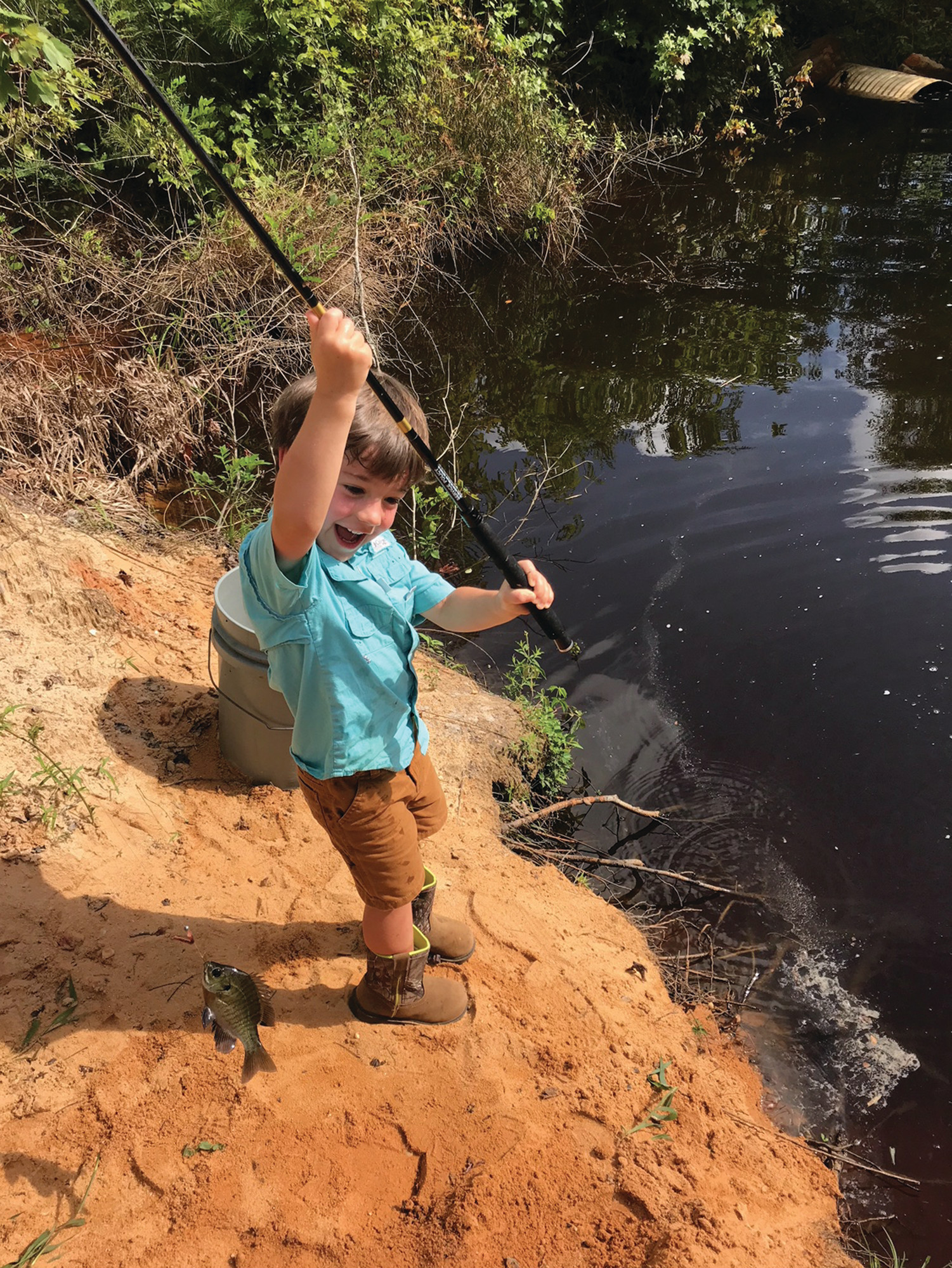 Shepherd Rowell, 3-year-old son of Michael and Kelly Rowell, reacts to his first catch (a bream) June 30 at a private pond in Pinewood.