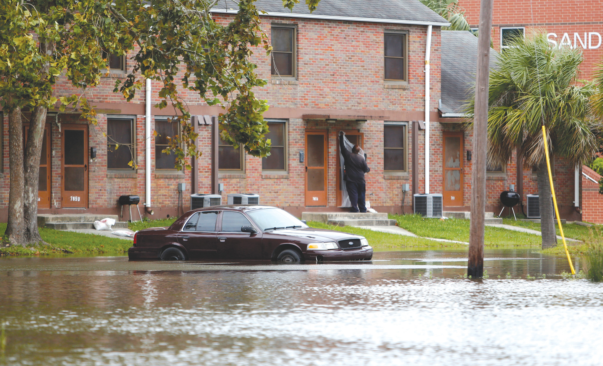 A Charleston resident puts plastic up over his apartment door as a car rests in floodwaters near East Bay Street in Charleston after Hurricane Irma on Sept. 10, 2017.