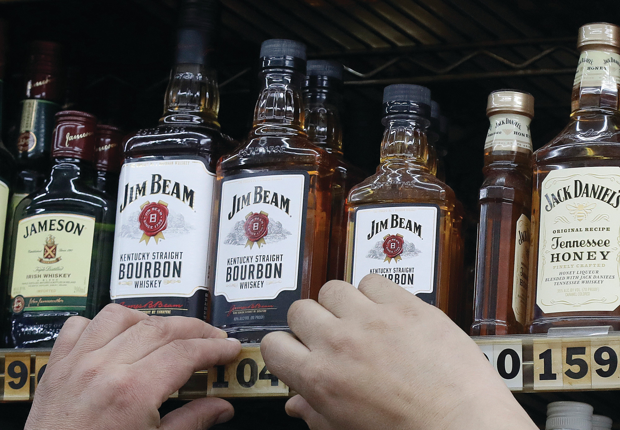 THE ASSOCIATED PRESSA man adjusts prices under bottles of Jim Beam bourbon whiskey displayed at Rossi's Deli in San Francisco. After the U.S. imposed 25 percent tariffs on $34 billion worth of Chinese goods, China retaliated by imposing tariffs on the same amount of U.S. products including whiskey.