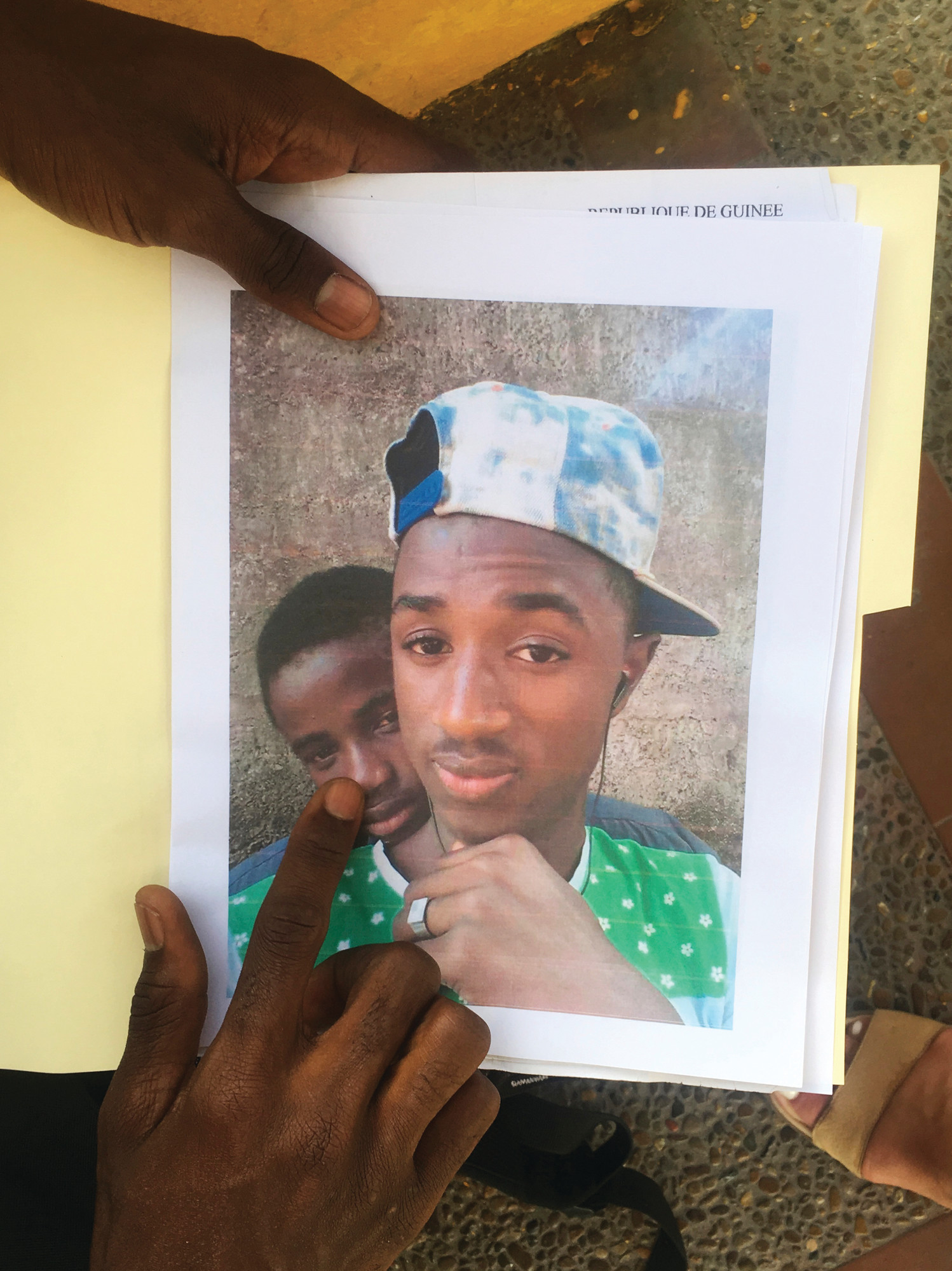 THE ASSOCIATED PRESSMamadou Aliou Barry, who departed from his native Guinea in West Africa when he was 14, a few years ago, shows a print of a selfie with his friend while waiting for entry to the U.S. on the Gateway Bridge in Matamoros, Mexico, which connects to Brownsville, Texas. He said as part of the minority ethnic Fula group, he fears for his life and carries this picture of him and a friend together and another picture of his friend after he was murdered, for his asylum interview.