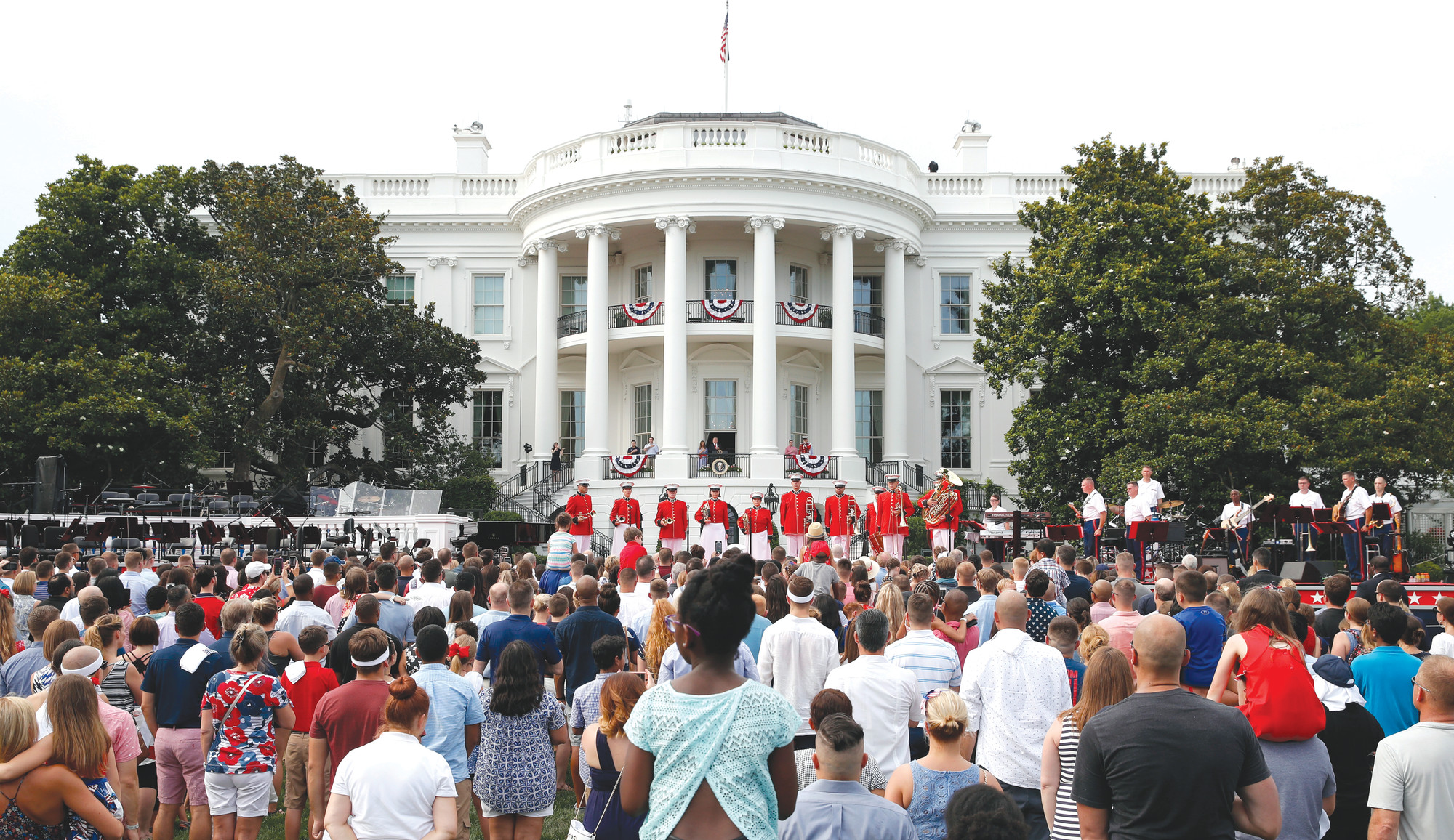 Visitors gather at the White House for the playing of the national anthem during an afternoon picnic for military families on the South Lawn of the White House on July 4 in Washington.