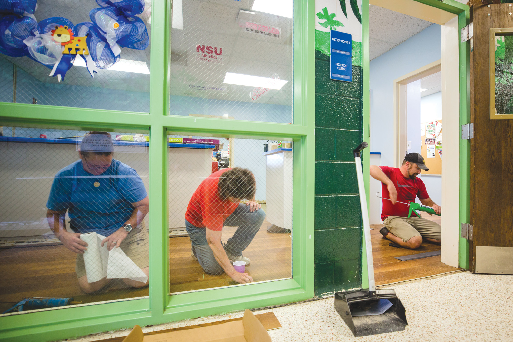 Lowe's Sumter employee volunteers finish off work in Lemira Elementary School's front reception area on Thursday.