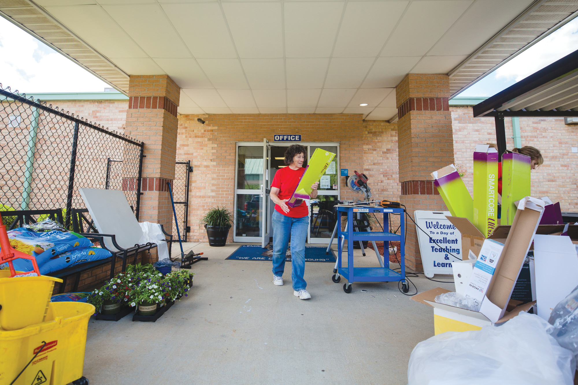 A Lowe's employee volunteer organizes donated supplies in front of Lemira Elementary School on Thursday.