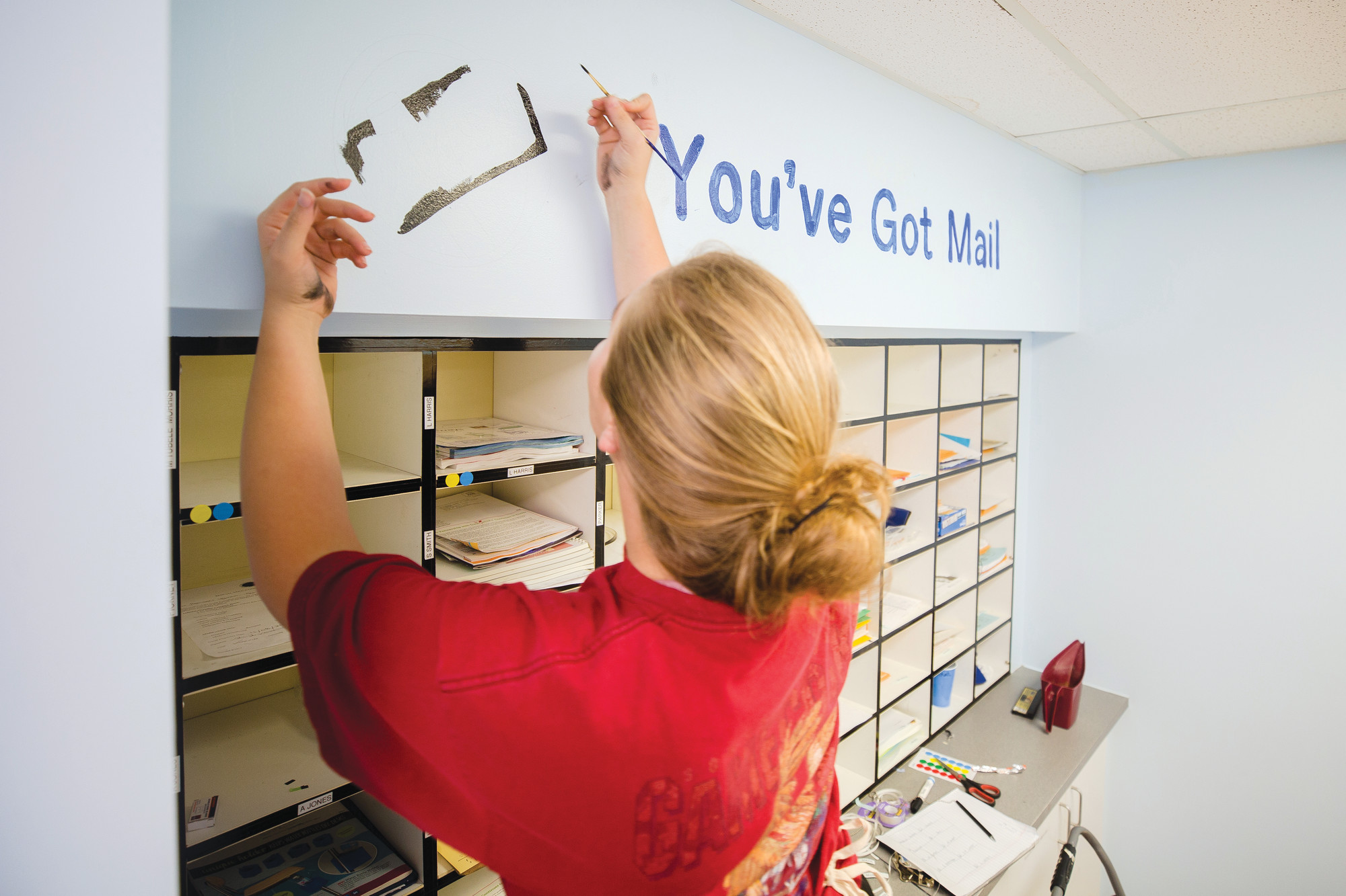 A Lowe's employee volunteer paints in the teacher mailbox area at Lemira on Thursday.