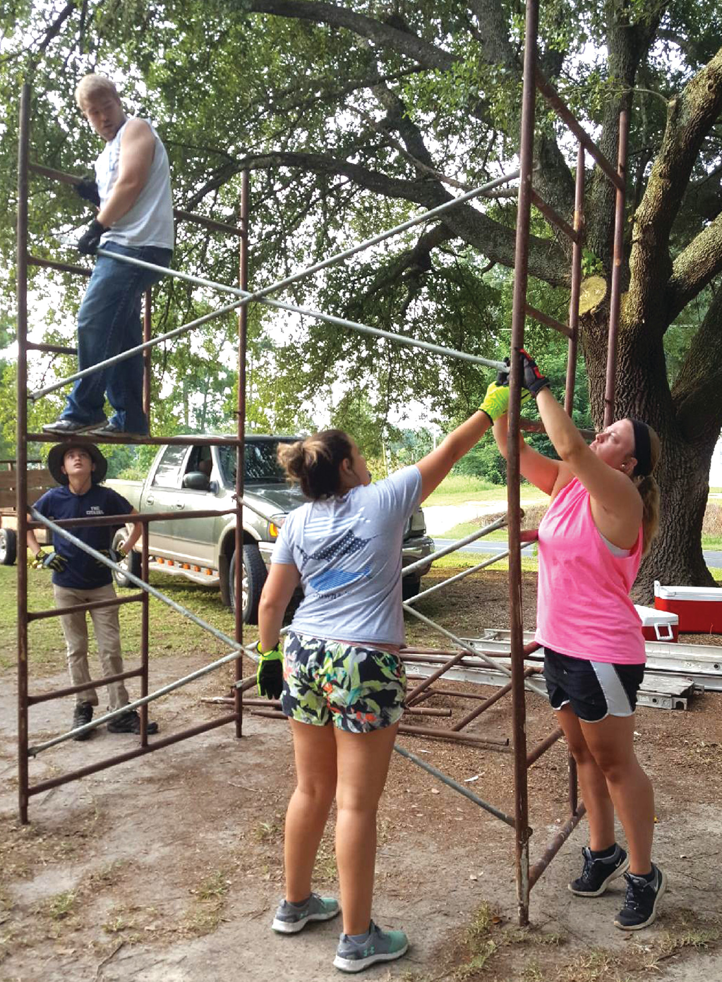 PHOTO PROVIDEDJessi Weir of Pinewood and two other Salkehatchie campers put together scaffolding before painting the exterior of a home during the week of July 15 in 