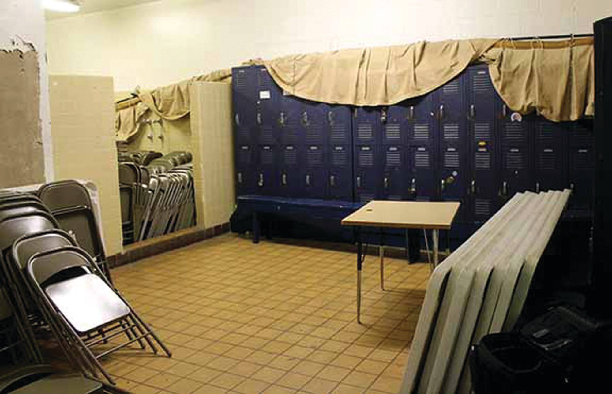 The picture taken in February 2018 shows that the dressing room serves a dual purpose: storage room for chairs and tables and outdated lockers and the dressing room for Wolverine boys' basketball teams.