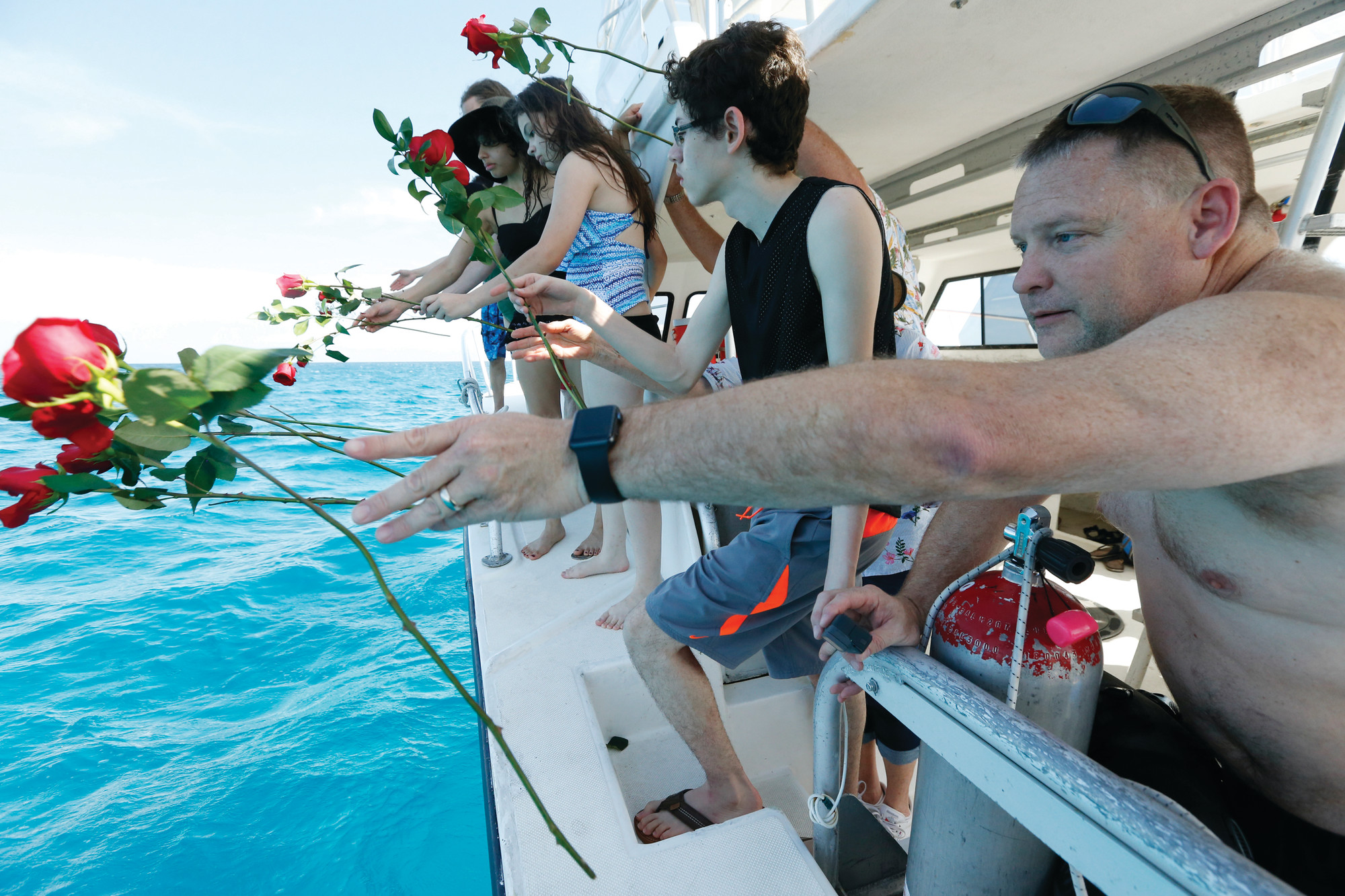 Will Payne, right, and three generations of his family throw flowers into the sea July 19 after a memorial plaque for Payne's parents, Buel and Linda Payne, was installed at the memorial reef.