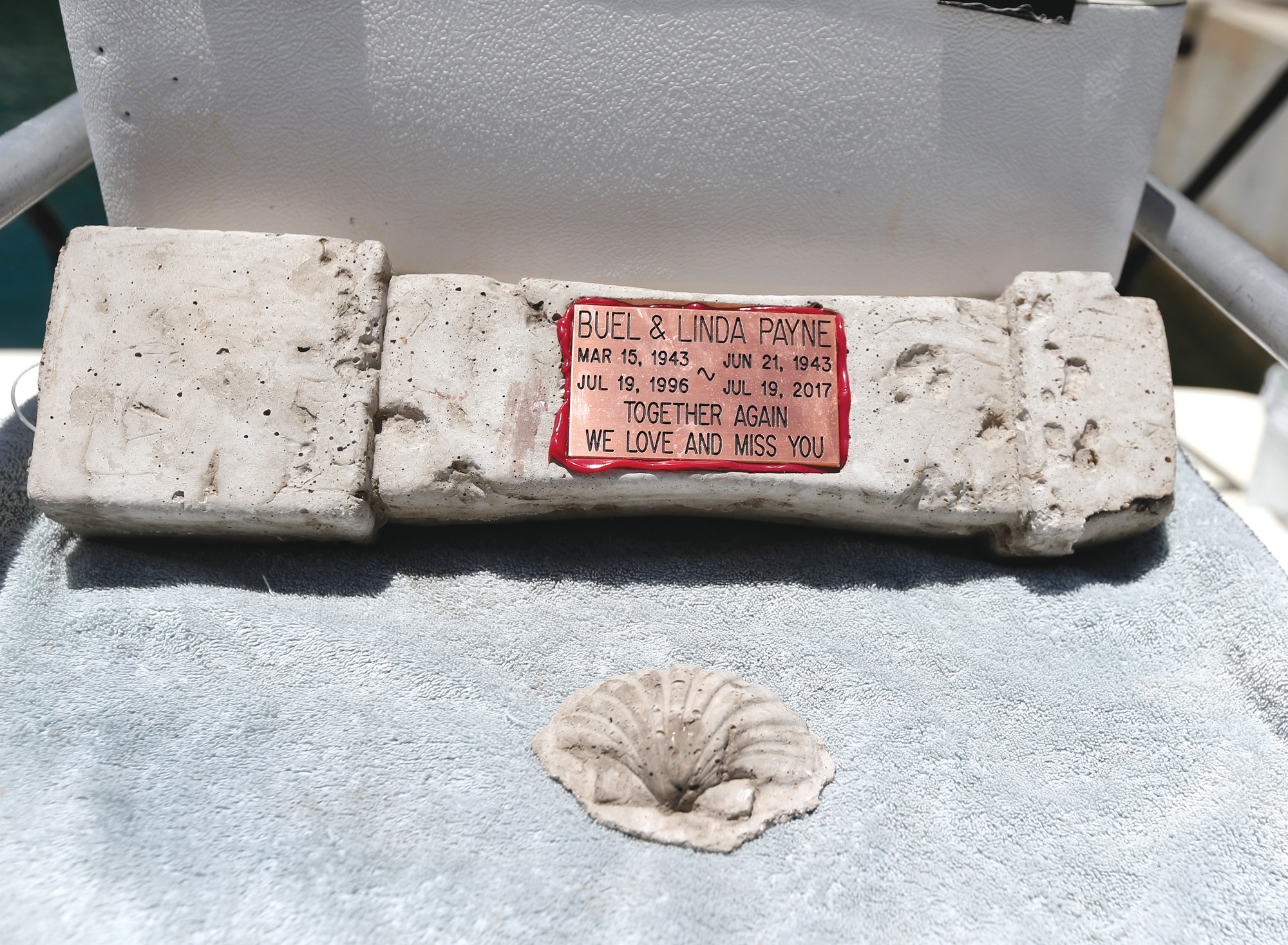 A memorial plaque for Buel and Linda Payne, affixed to a cement baluster mixed with their ashes, is displayed near Miami Beach.