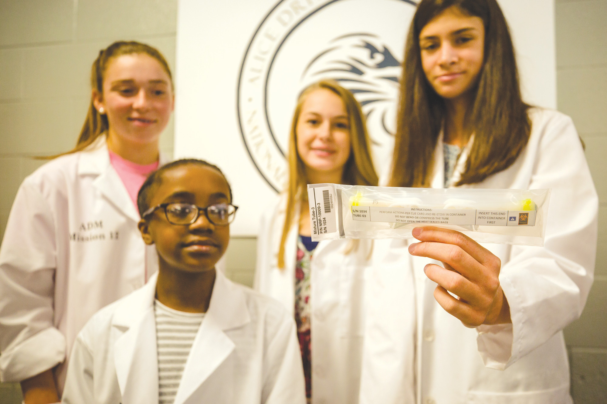Rising seventh-grader Alyse King, right, of the all-girls science team at Alice Drive Middle School, holds the spaceflight   experiments program project after it was opened Friday in a special ceremony at the school. Teammates, from left, are   Mary Brooke Mooneyham, Alana Garrick and Ashlin Farmer.