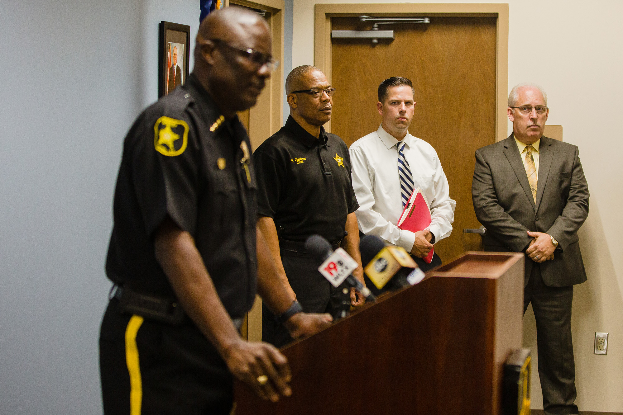Sumter County Sheriff Anthony Dennis addresses media Monday as investigators look on during a press conference about a suspect who fled the area after a fatal shooting at a Sumter auto body repair shop.