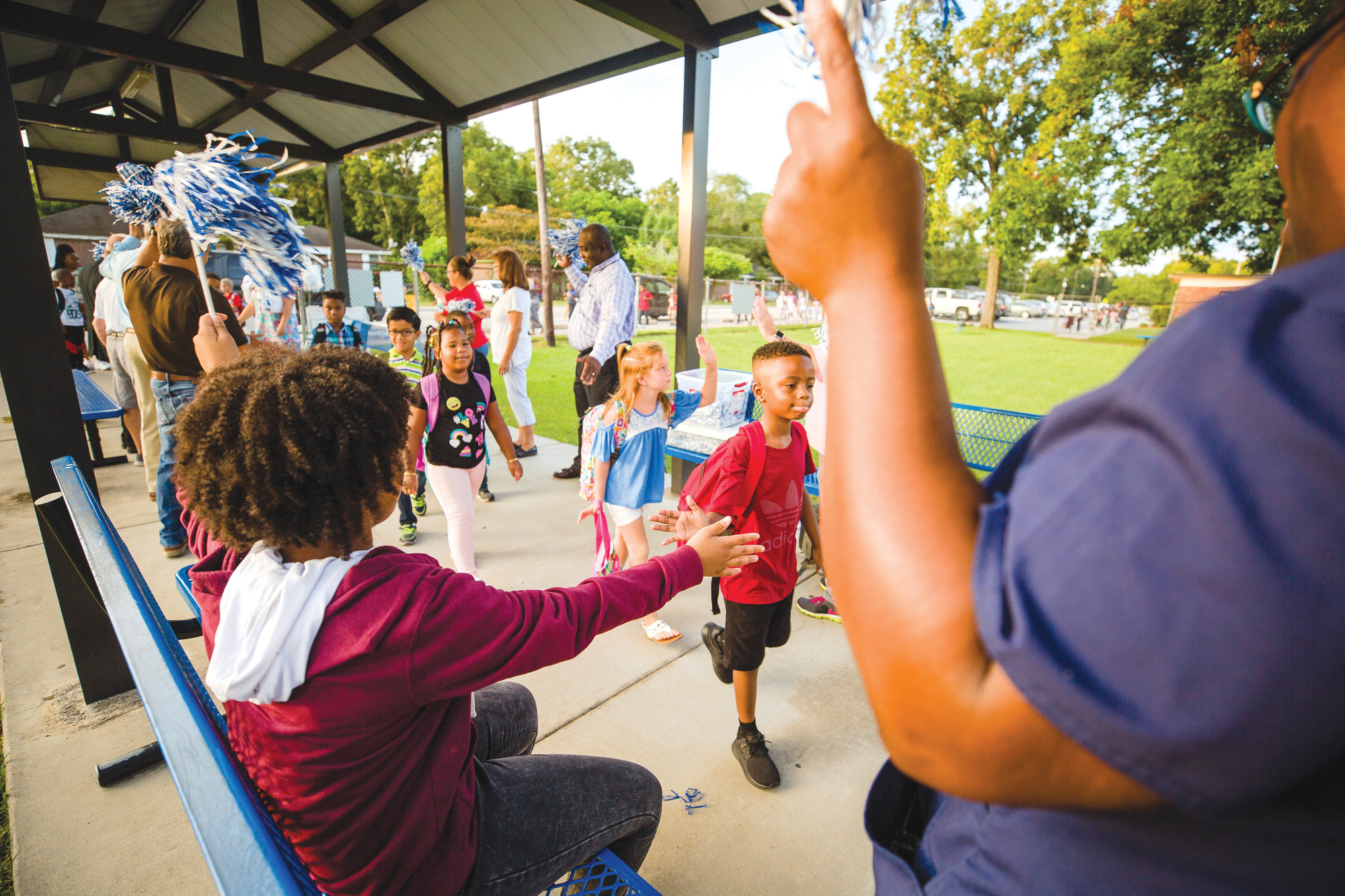 Students at Willow Drive Elementary School are cheered on as they walk into the school for their first day on Monday.