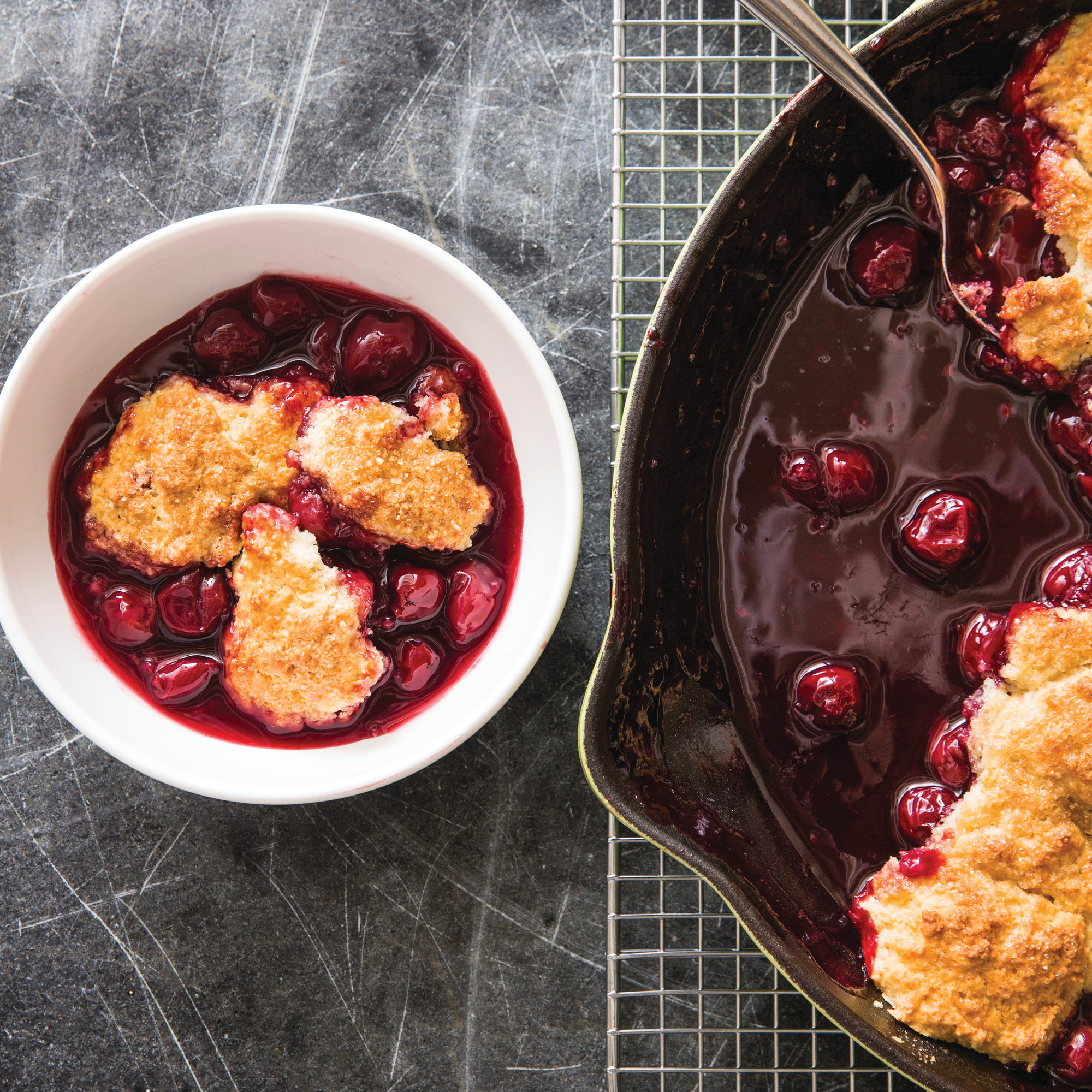 "This undated photo provided by America's Test Kitchen in July 2018 shows a cherry cobbler in Brookline, Massachusetts. This recipe appears in the cookbook ""Cook It In Cast Iron."""
