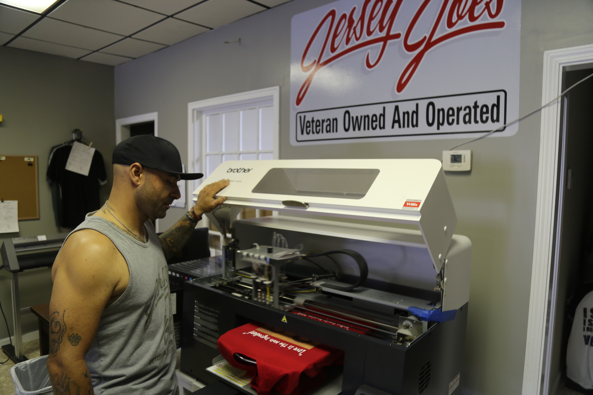BRUCE MILLS / THE SUMTER ITEMJoe Davies watches a T-shirt go through his direct-to-garment printer on Thursday at his downtown shop. A U.S. Army veteran, Davies will mark the one-year anniversary of his custom-apparel shop on Saturday with a sidewalk sale.