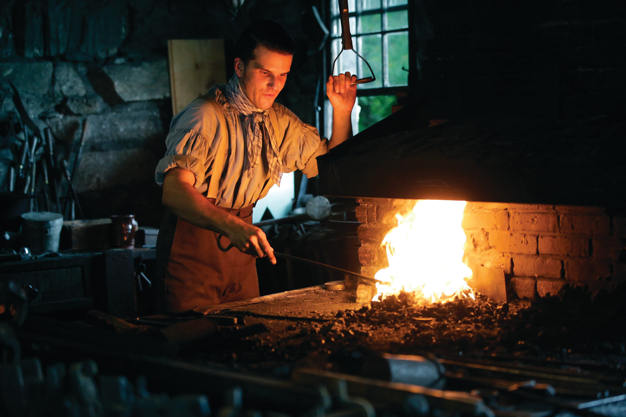 PHOTOS BY THE ASSOCIATED PRESSDerek Heidemann reenacts an 1830s blacksmith at Old Sturbridge Village, in Sturbridge, Massachusetts, on Aug. 22. With a $75,000 grant from the National Endowment for the Humanities, Old Sturbridge Village, a living history museum that depicts life in a small New England town in the 1830s, is taking a deep look at the way it presents the past, including the roles of minorities and women, in an effort to stay relevant to a 21st-century audience.
