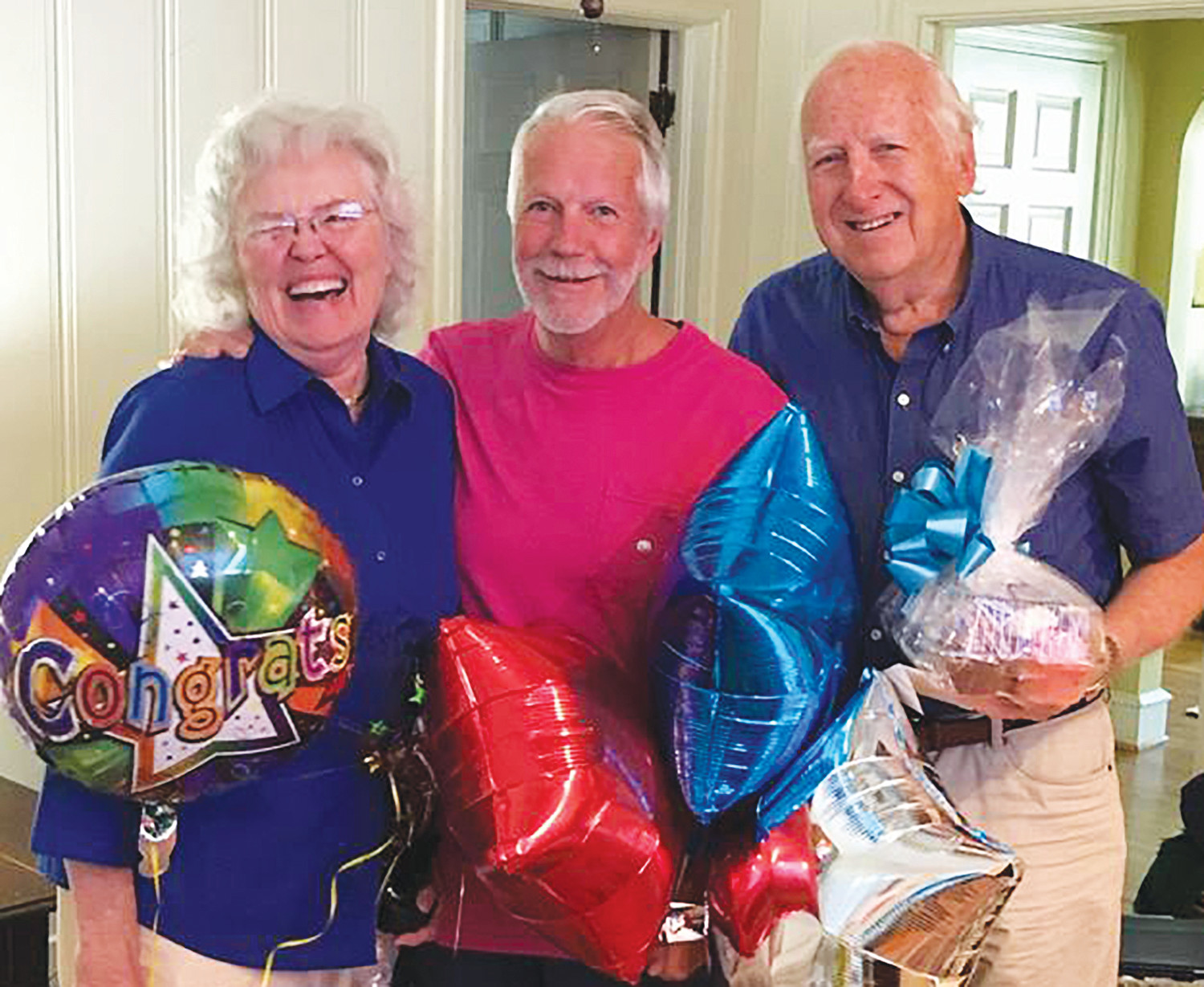 W. Louis Griffith, center, who received the Clarendon County Chamber of Commerce's Ambassador of the Year award, was surprised with balloons and a gift from Carole and George Summers after he was announced as this year's award recipient.