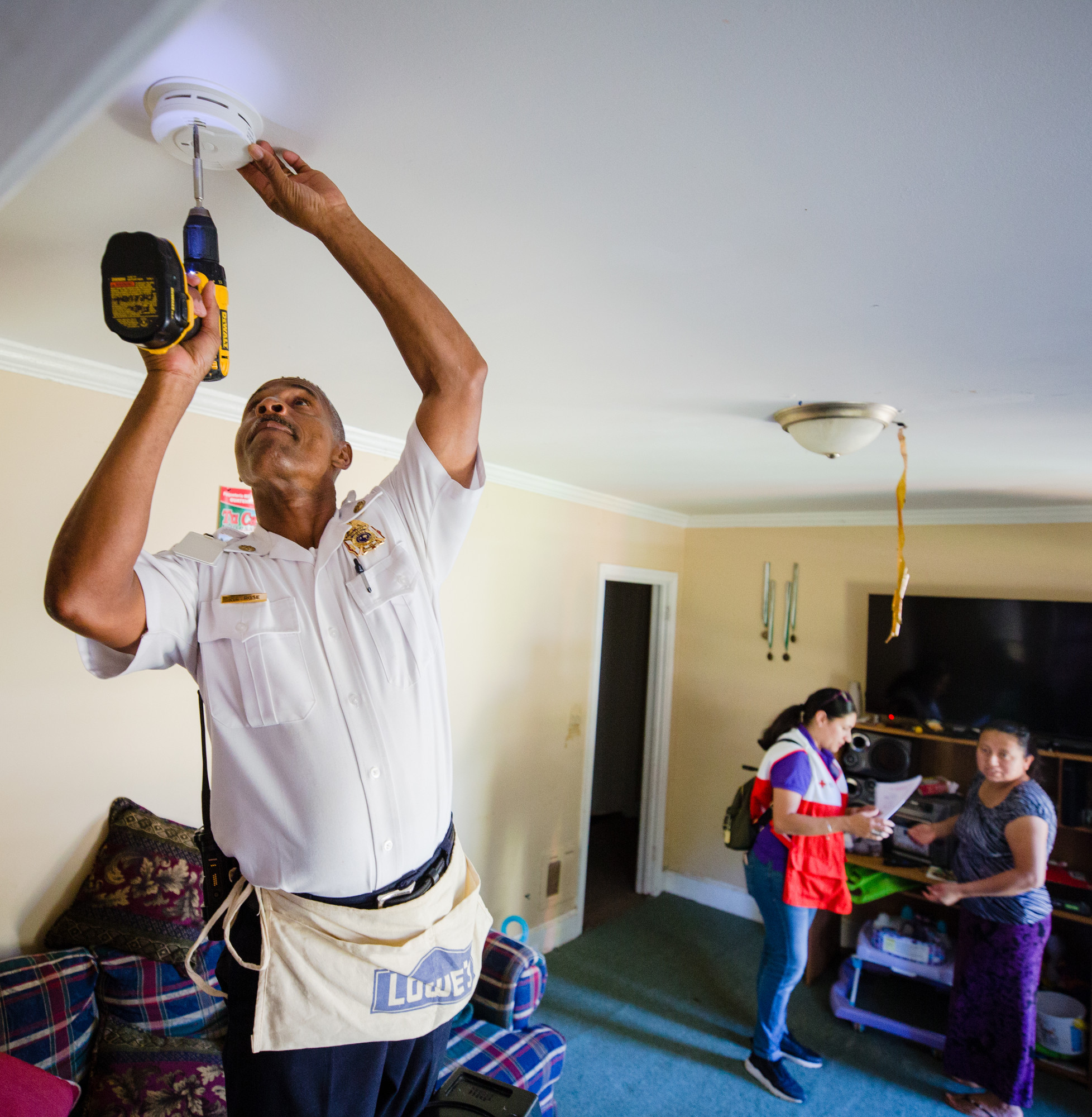 Sumter Fire Department Division Chief Johnnie Rose installs a smoke detector in a home near Crosswell Drive.