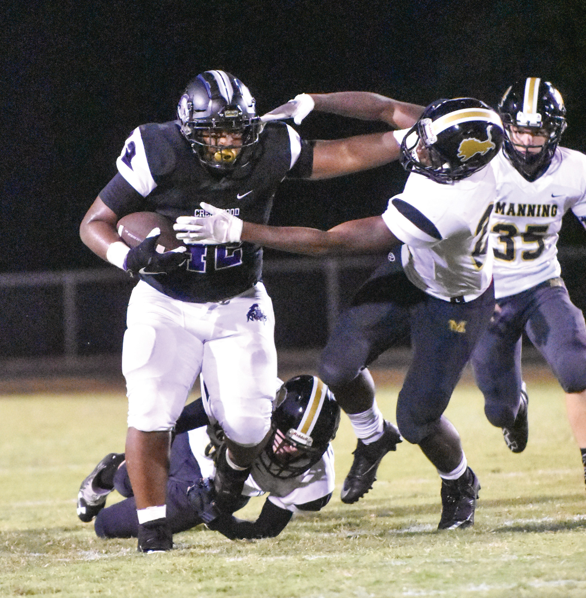 Crestwood running back Chris Haynesworth (42) delivers a stiff-arm to Manning defender Anthony Gibbs (22) during the third quarter of the Knights' 14-7 loss to the Monarchs on Friday at Donald L. Crolley Memorial Stadium in Dalzell.